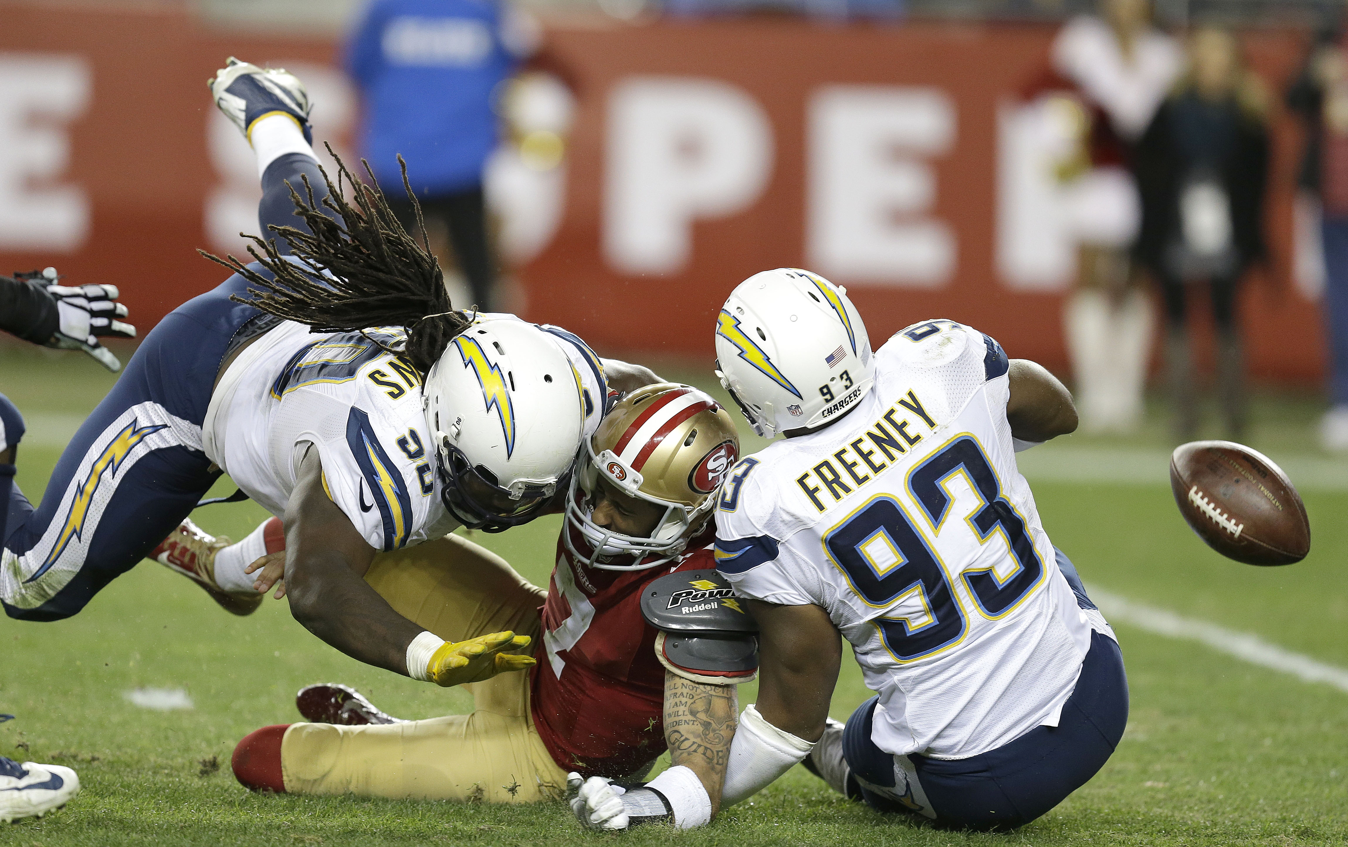 San Francisco 49ers quarterback Colin Kaepernick, center, fumbles the ball after being sacked by San Diego Chargers outside linebacker Dwight Freeney (93) and defensive tackle Ricardo Mathews (90) during the third quarter of an NFL football game in Santa