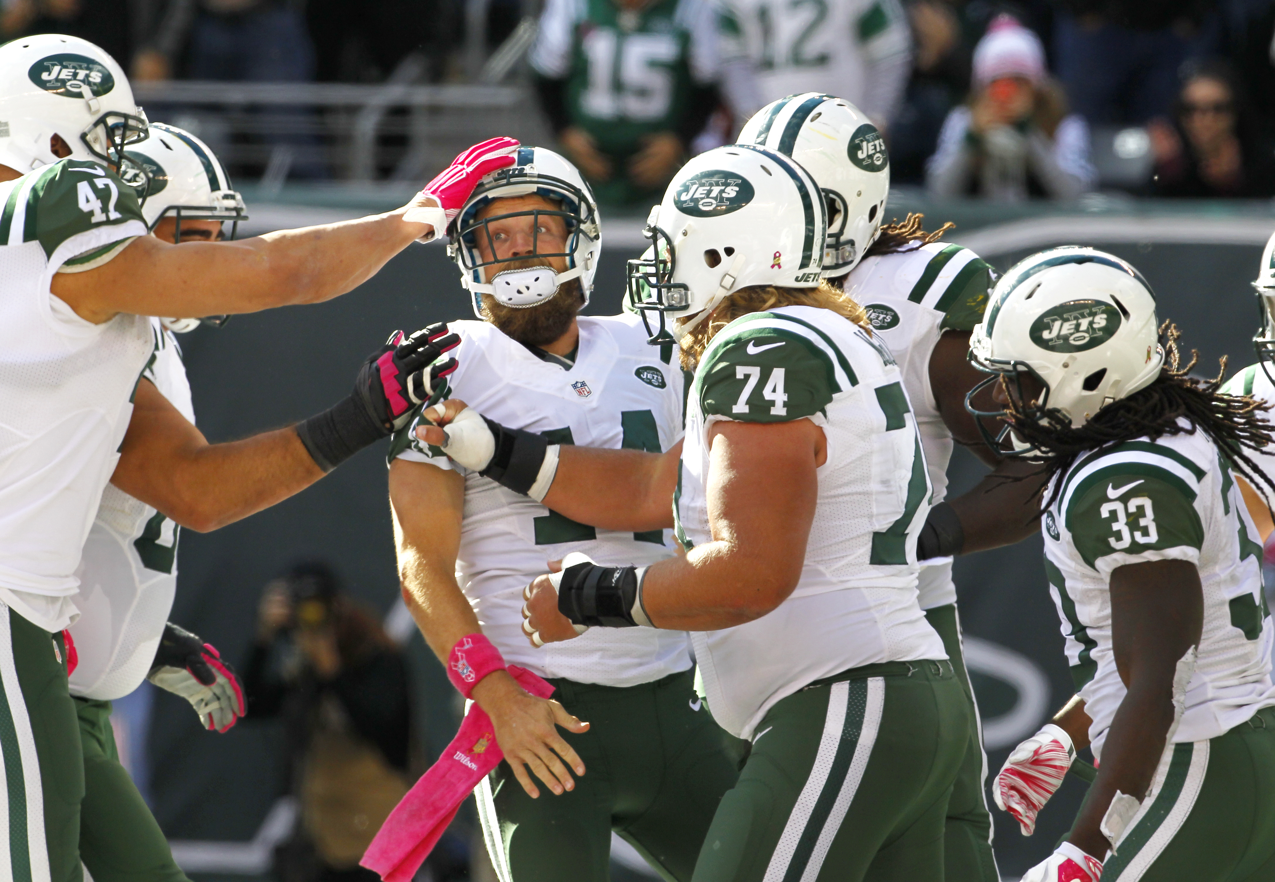 New York Jets quarterback Ryan Fitzpatrick, center left, is mobbed by teammates after scoring a touchdown run against the Washington Redskins during the second half of an NFL football game, Sunday, Oct. 18, 2015, in East Rutherford, N.J. (AP Photo/Gary He
