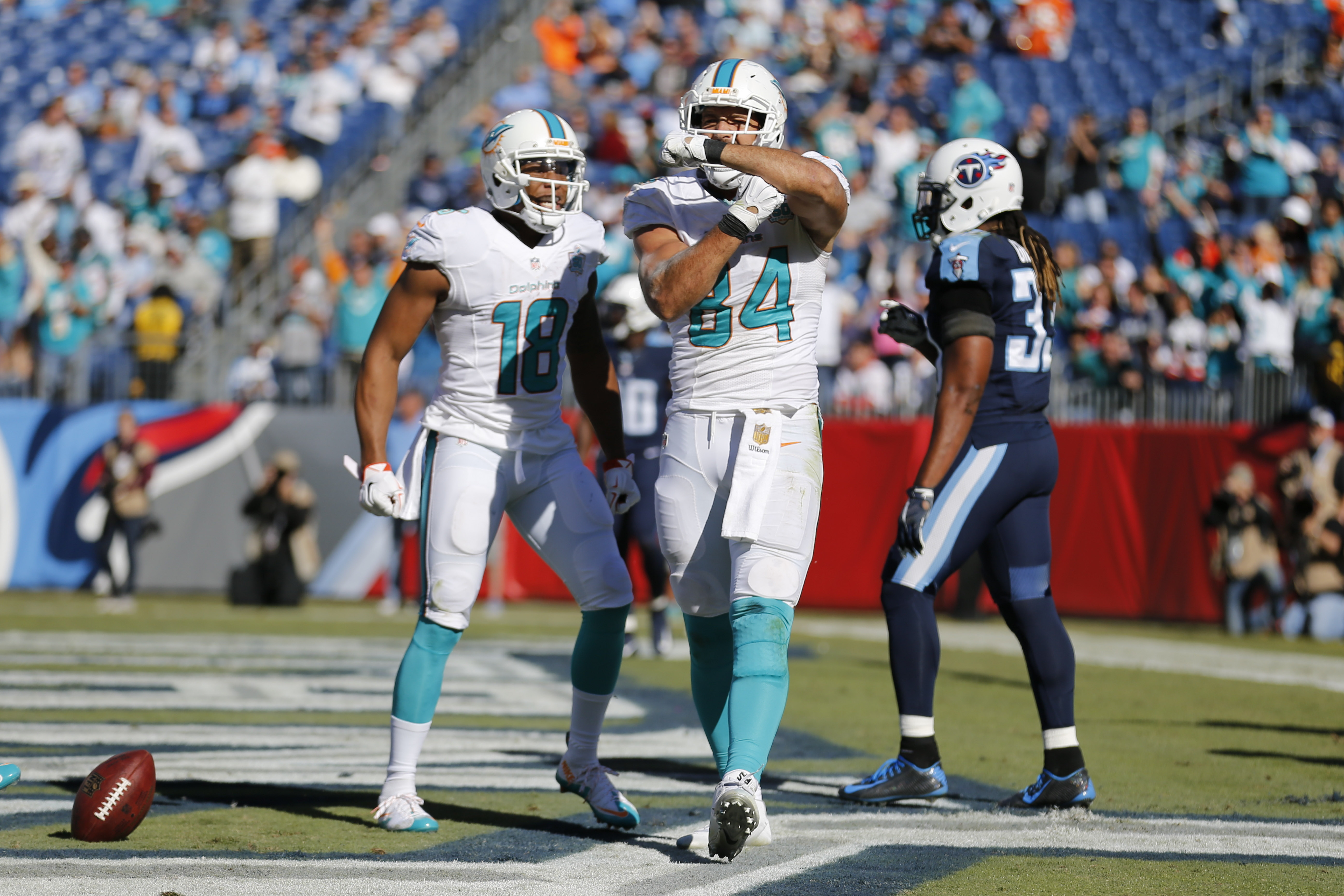 Miami Dolphins tight end Jordan Cameron (84) celebrates after catching a 12-yard touchdown pass against the Tennessee Titans in the second half of an NFL football game Sunday, Oct. 18, 2015, in Nashville, Tenn. At left is Dolphins wide receiver Rishard Ma