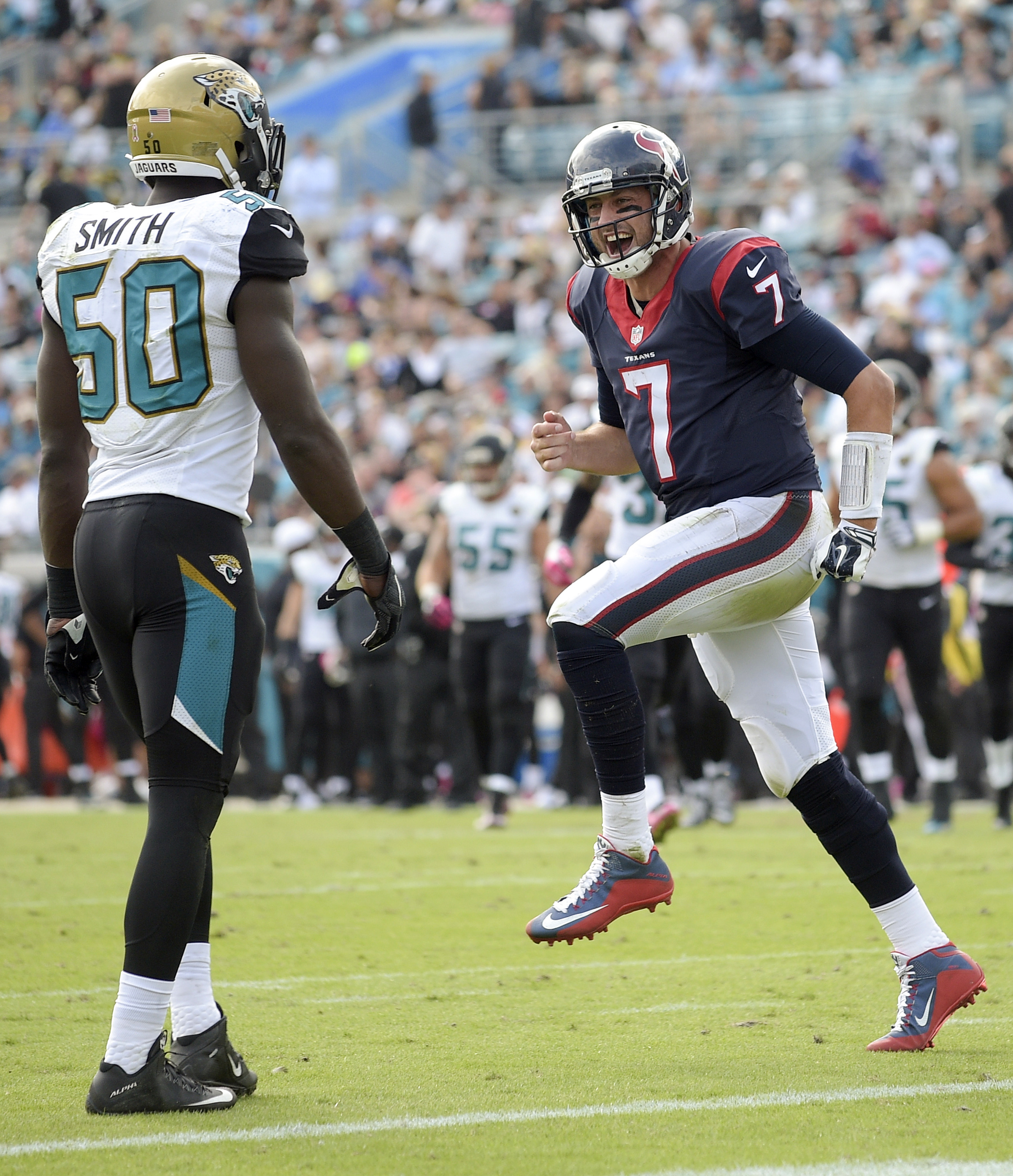 Houston Texans quarterback Brian Hoyer (7) celebrates in front of Jacksonville Jaguars outside linebacker Telvin Smith (50) after throwing a touchdown pass during the second half of an NFL football game in Jacksonville, Fla., Sunday, Oct. 18, 2015. (AP Ph