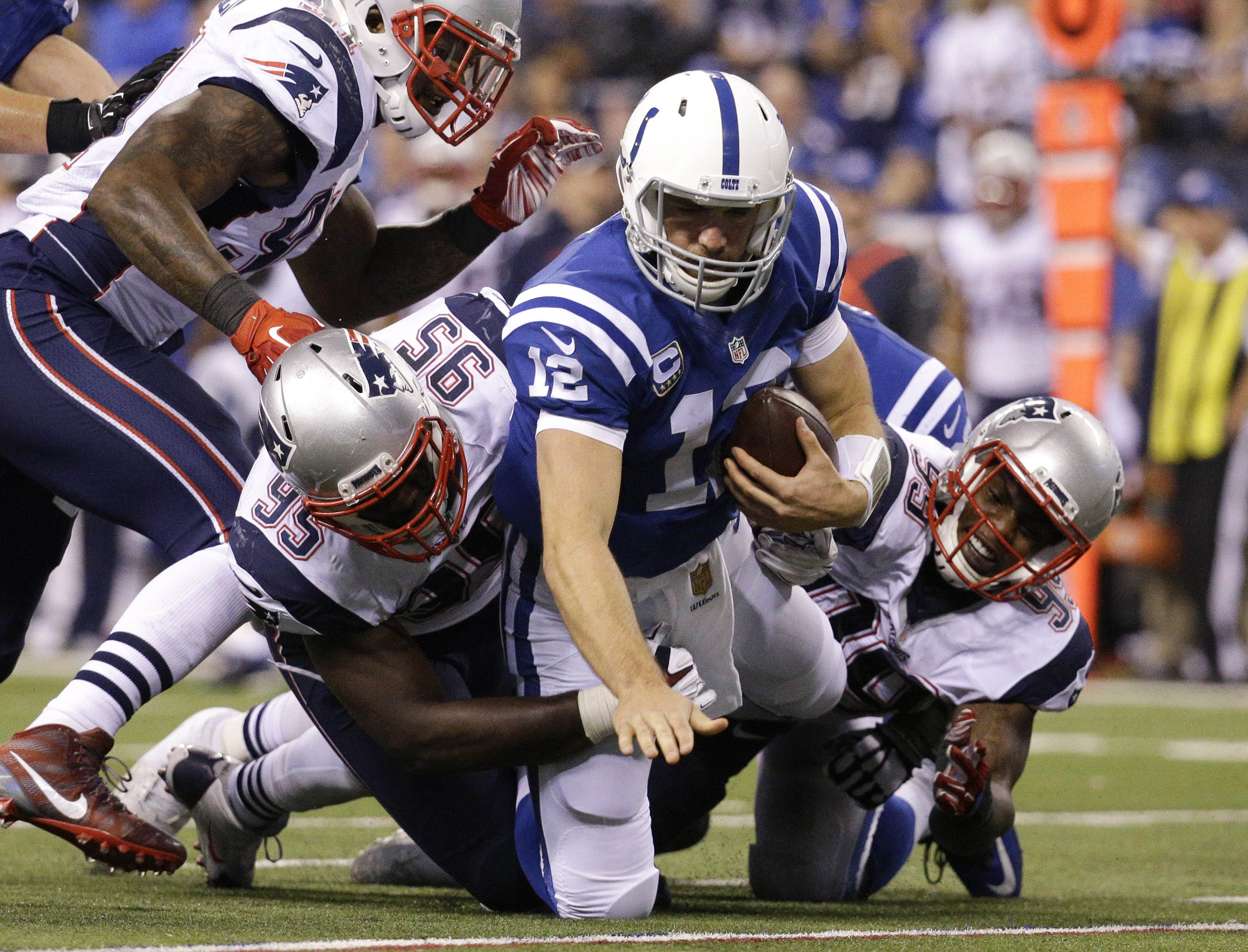 Indianapolis Colts quarterback Andrew Luck (12) is sacked by New England Patriots defensive end Chandler Jones (95) and defensive tackle Dominique Easley (99) in the second half of an NFL football game in Indianapolis, Sunday, Oct. 18, 2015. New England w