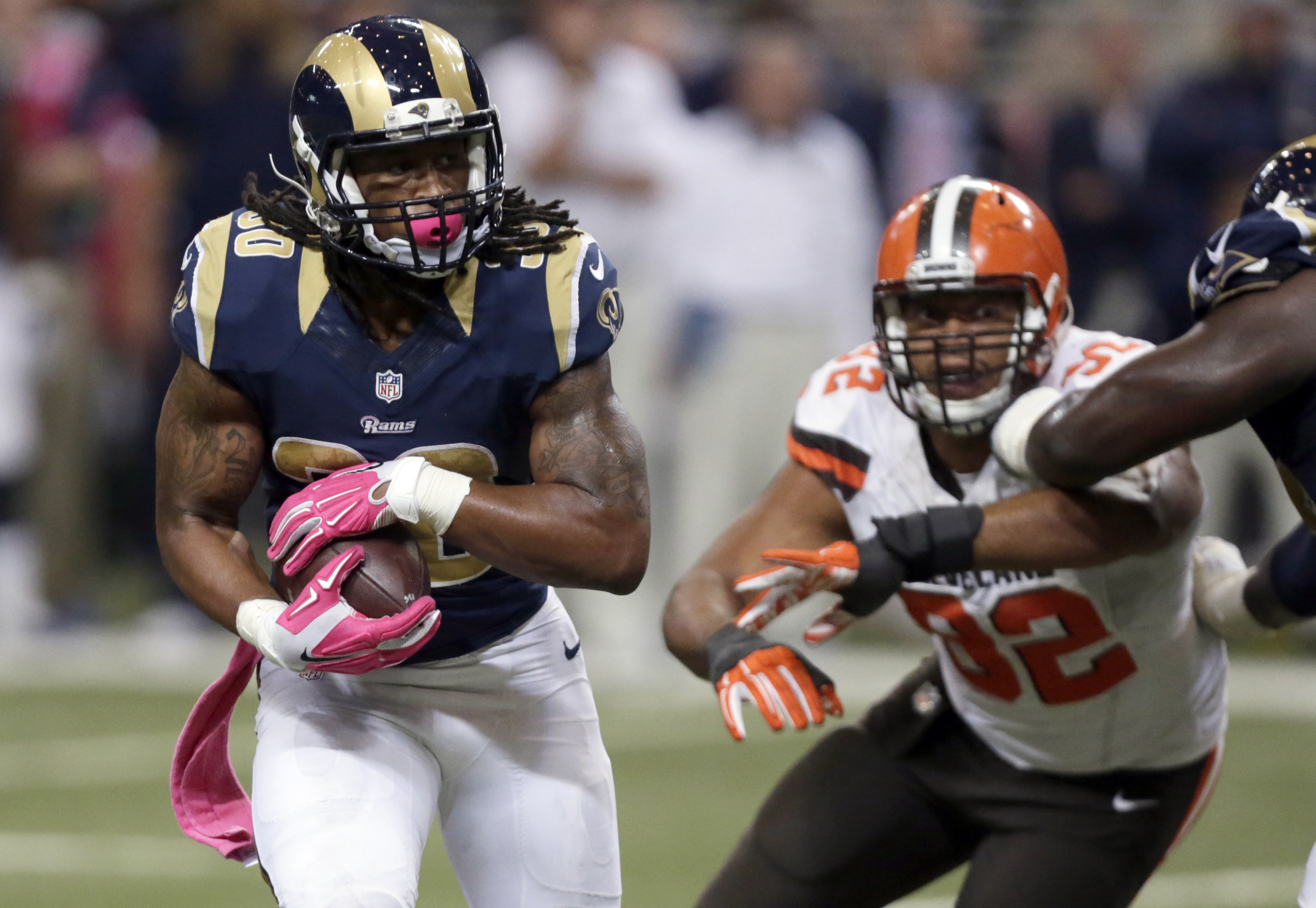 St. Louis Rams running back Todd Gurley, left, runs past Cleveland Browns defensive end Desmond Bryant on his way to a 16-yard touchdown run during the fourth quarter of an NFL football game Sunday, Oct. 25, 2015, in St. Louis. (AP Photo/Tom Gannam)
