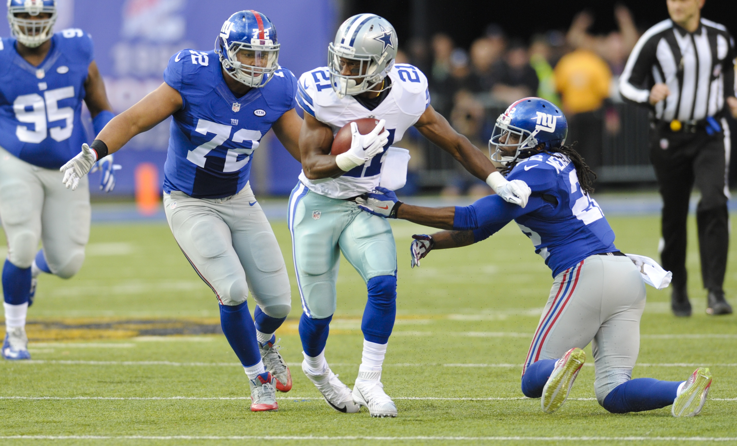 Dallas Cowboys' Joseph Randle (21) breacks a tackle by New York Giants' Brandon Meriweather (22) during the first half of an NFL football game, Sunday, Oct. 25, 2015, in East Rutherford, N.J. (AP Photo/Bill Kostroun)