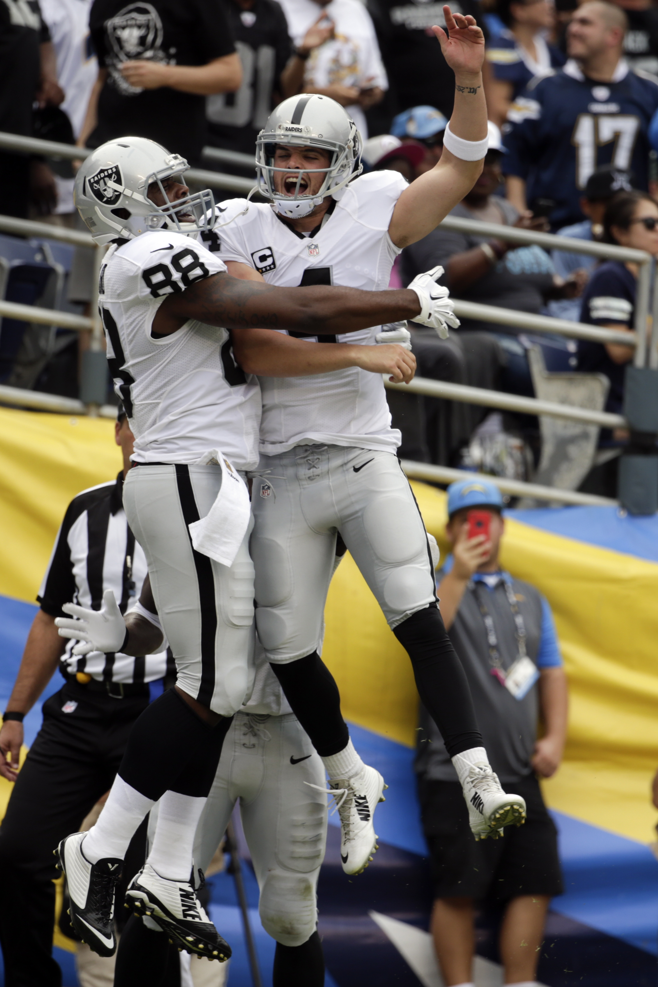 Oakland Raiders quarterback Derek Carr, right, and tight end Clive Walford celebrate after Walford's touchdown during the first half of an NFL football game against the San Diego Chargers  Sunday, Oct. 25, 2015, in San Diego. (AP Photo/Lenny Ignelzi)