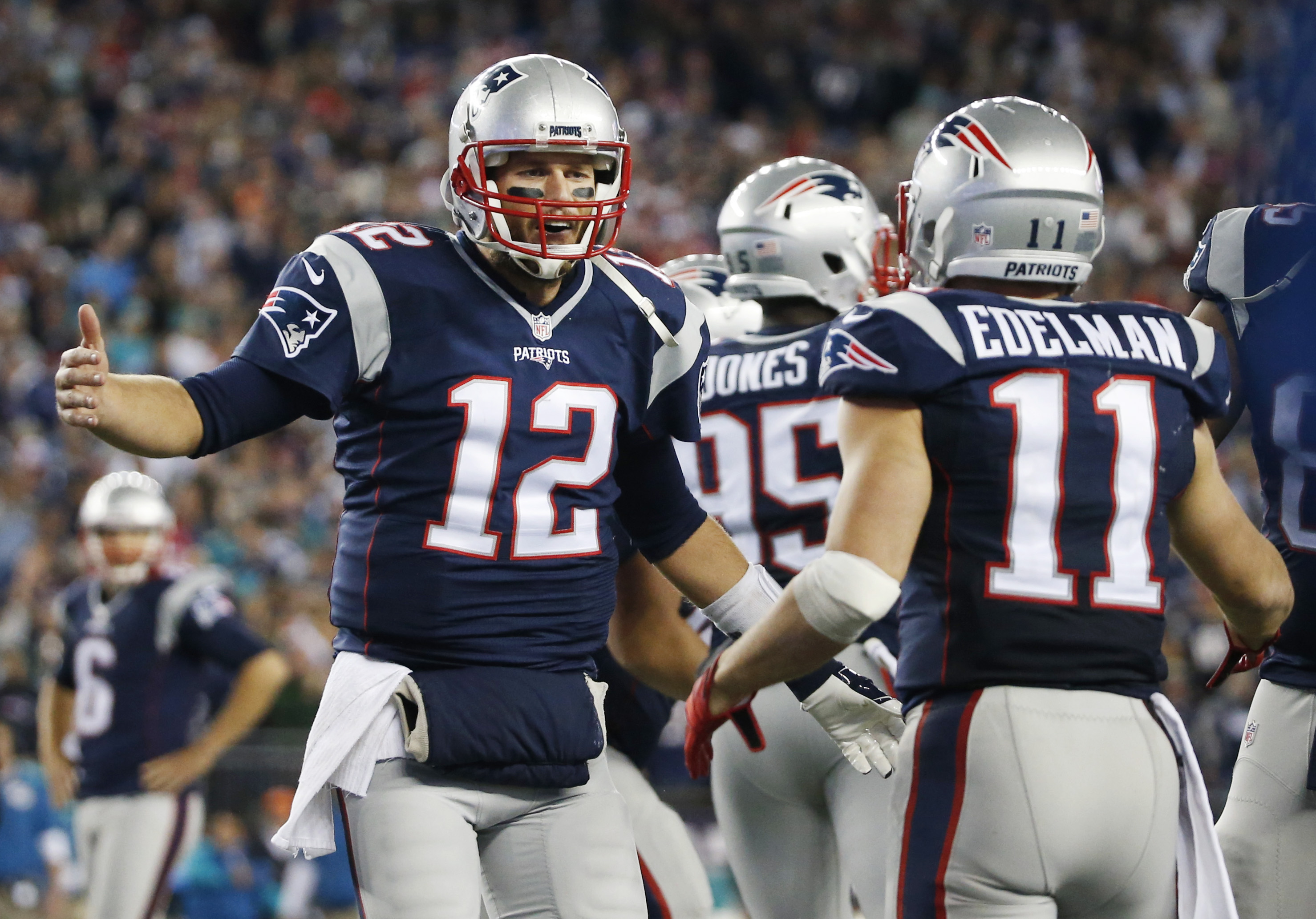 New England Patriots quarterback Tom Brady (12) celebrates his touchdown pass to wide receiver Julian Edelman (11) in the second half of an NFL football game against the Miami Dolphins, Thursday, Oct. 29, 2015, in Foxborough, Mass. (AP Photo/Michael Dwyer