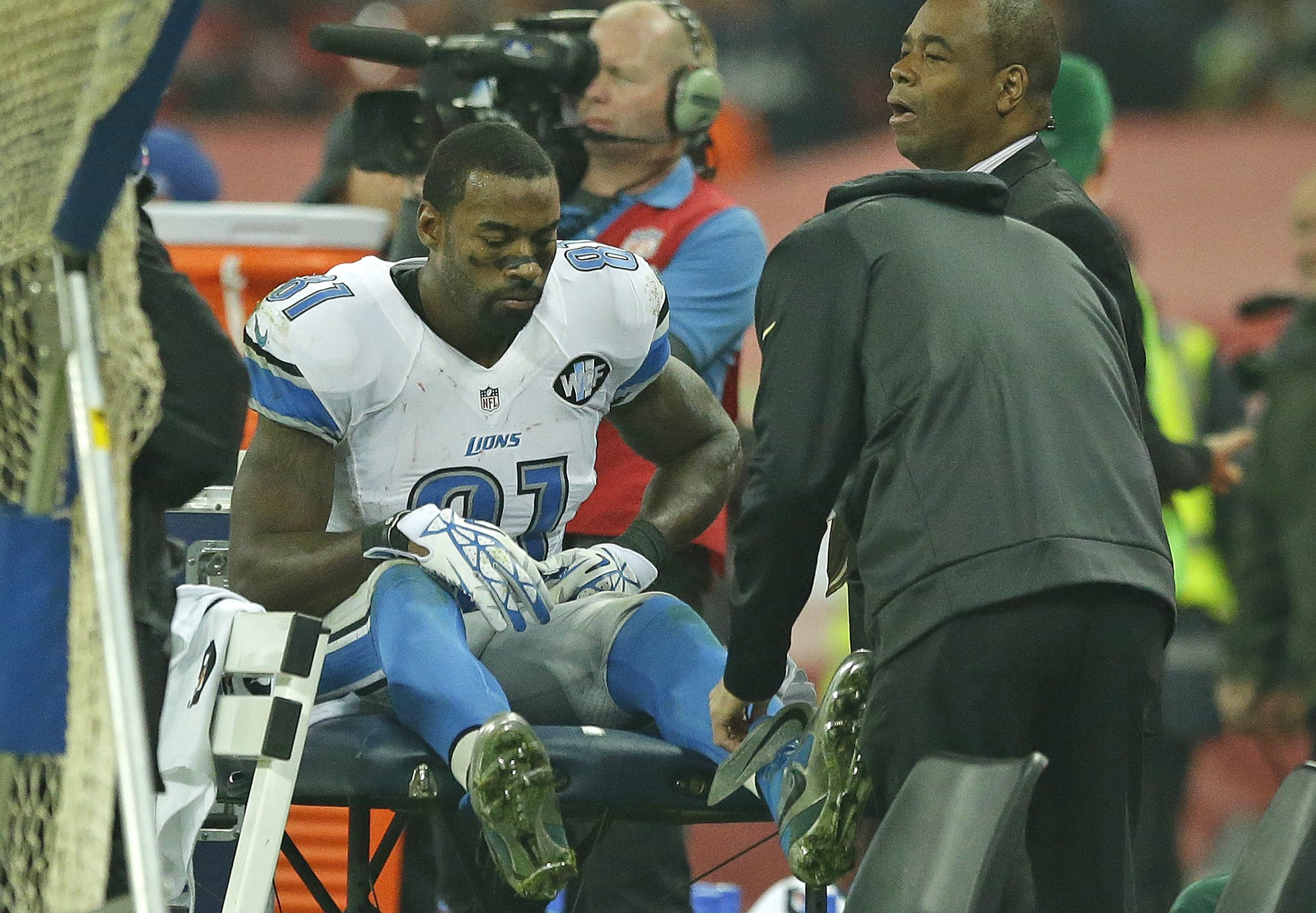 A medic checks the ankle of Detroit Lions' Calvin Johnson (81) on the sideline during the NFL football game between Detroit Lions and Kansas City Chiefs Wembley Stadium in London,  Sunday, Nov. 1, 2015. Chiefs won the match 45-10. (AP Photo/Matt Dunham)