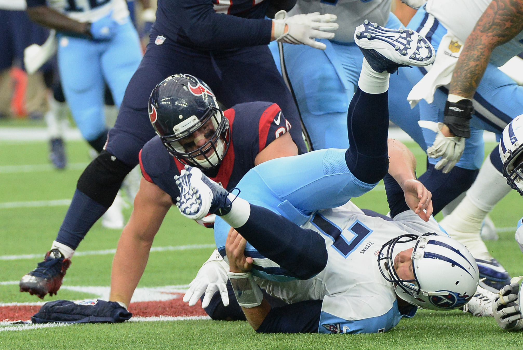 Tennessee Titans quarterback Zach Mettenberger (7) is upended by Houston Texans defensive end J.J. Watt (99) during the first half of an NFL football game, Sunday, Nov. 1, 2015, in Houston. (AP Photo/George Bridges)