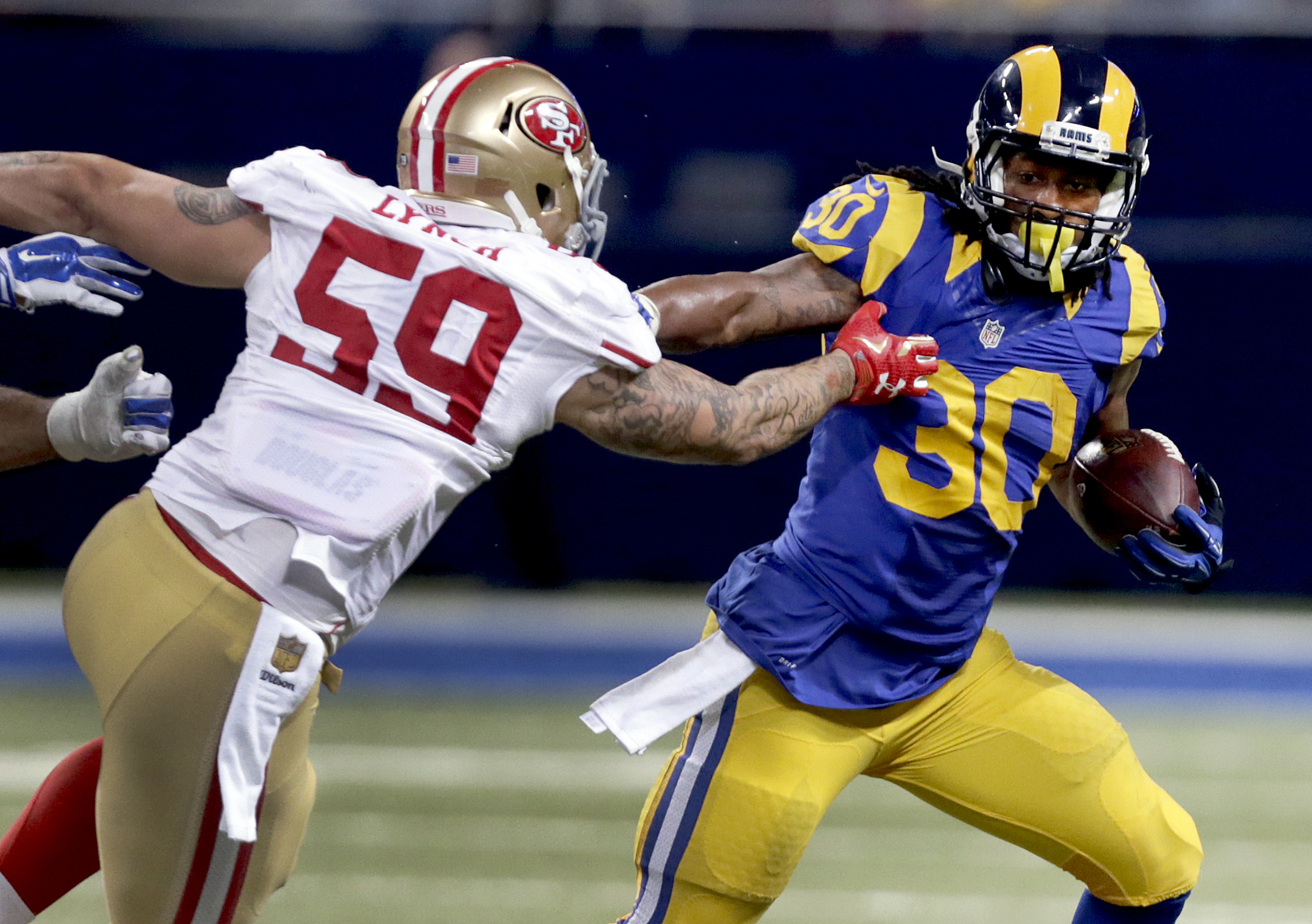 St. Louis Rams running back Todd Gurley, right, runs with the ball as San Francisco 49ers outside linebacker Aaron Lynch defends during the third quarter of an NFL football game Sunday, Nov. 1, 2015, in St. Louis. (AP Photo/Tom Gannam)