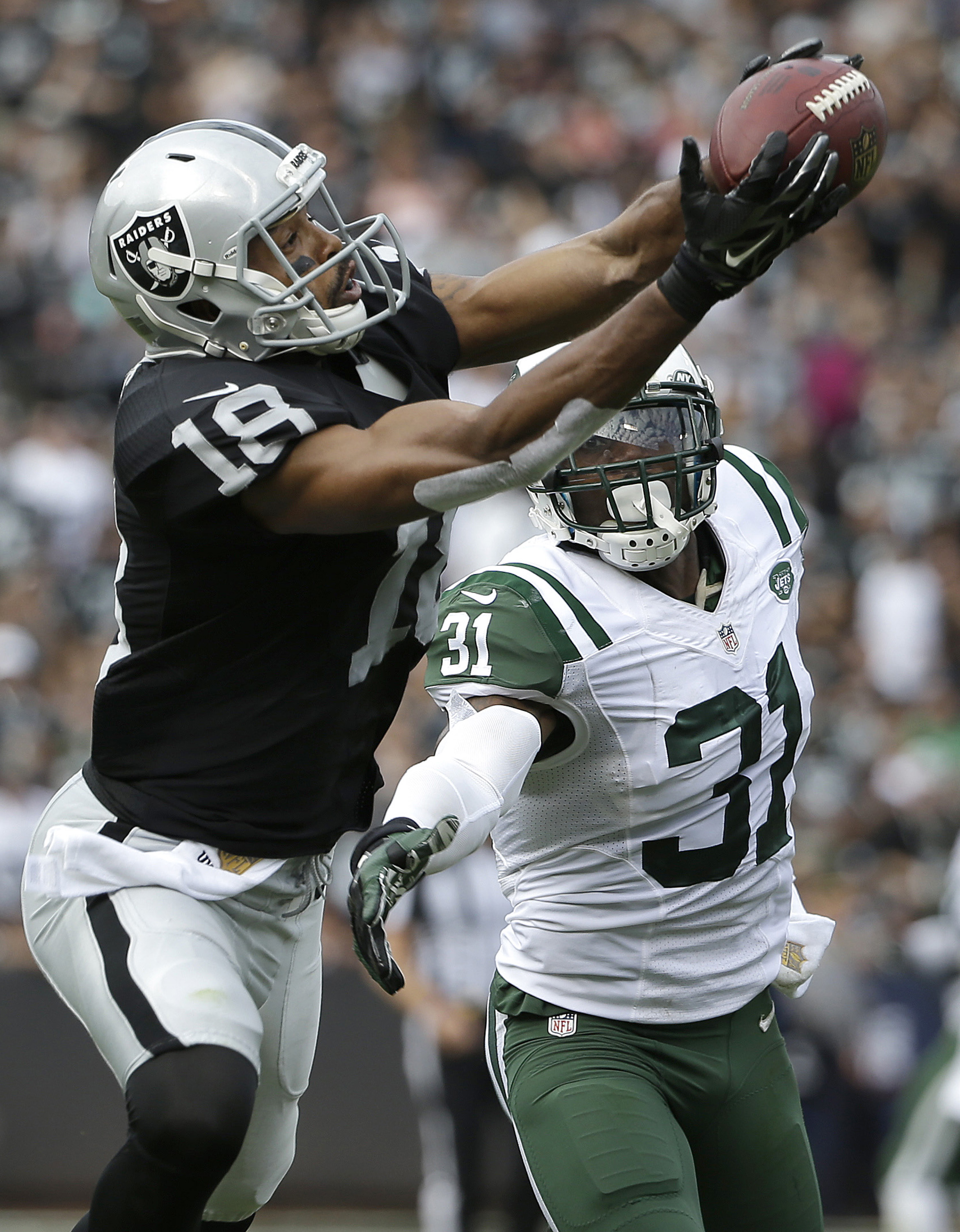 Oakland Raiders wide receiver Andre Holmes (18) catches a touchdown pass over New York Jets cornerback Antonio Cromartie (31) during the first half of an NFL football game in Oakland, Calif., Sunday, Nov. 1, 2015. (AP Photo/Marcio Jose Sanchez)