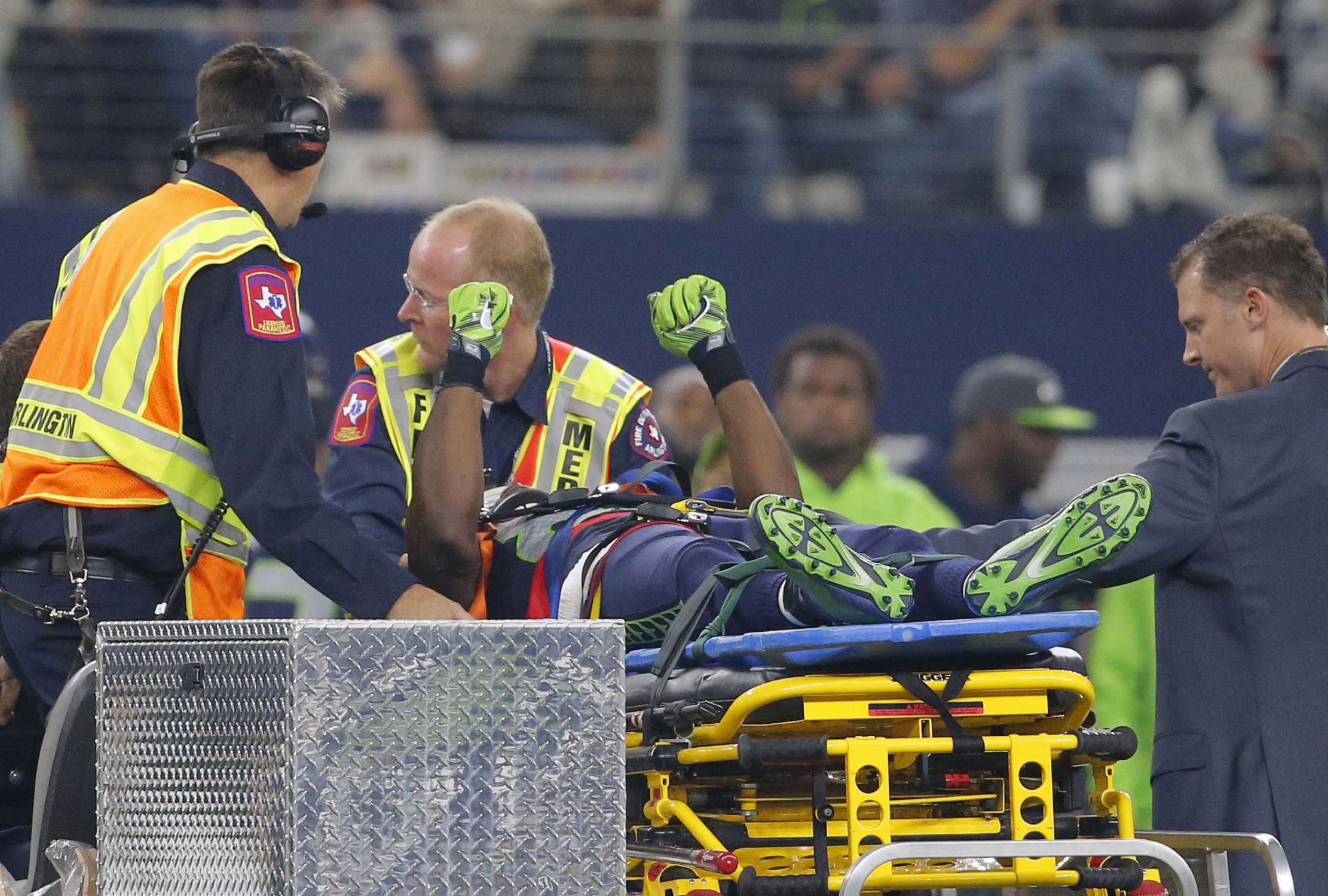 Seattle Seahawks' Ricardo Lockette holds up his hands as medical crew cart him off the field after suffering an unknown injury in the first half of an NFL football game against the Dallas Cowboys, Sunday, Nov. 1, 2015, in Arlington, Texas. (AP Photo/Brand