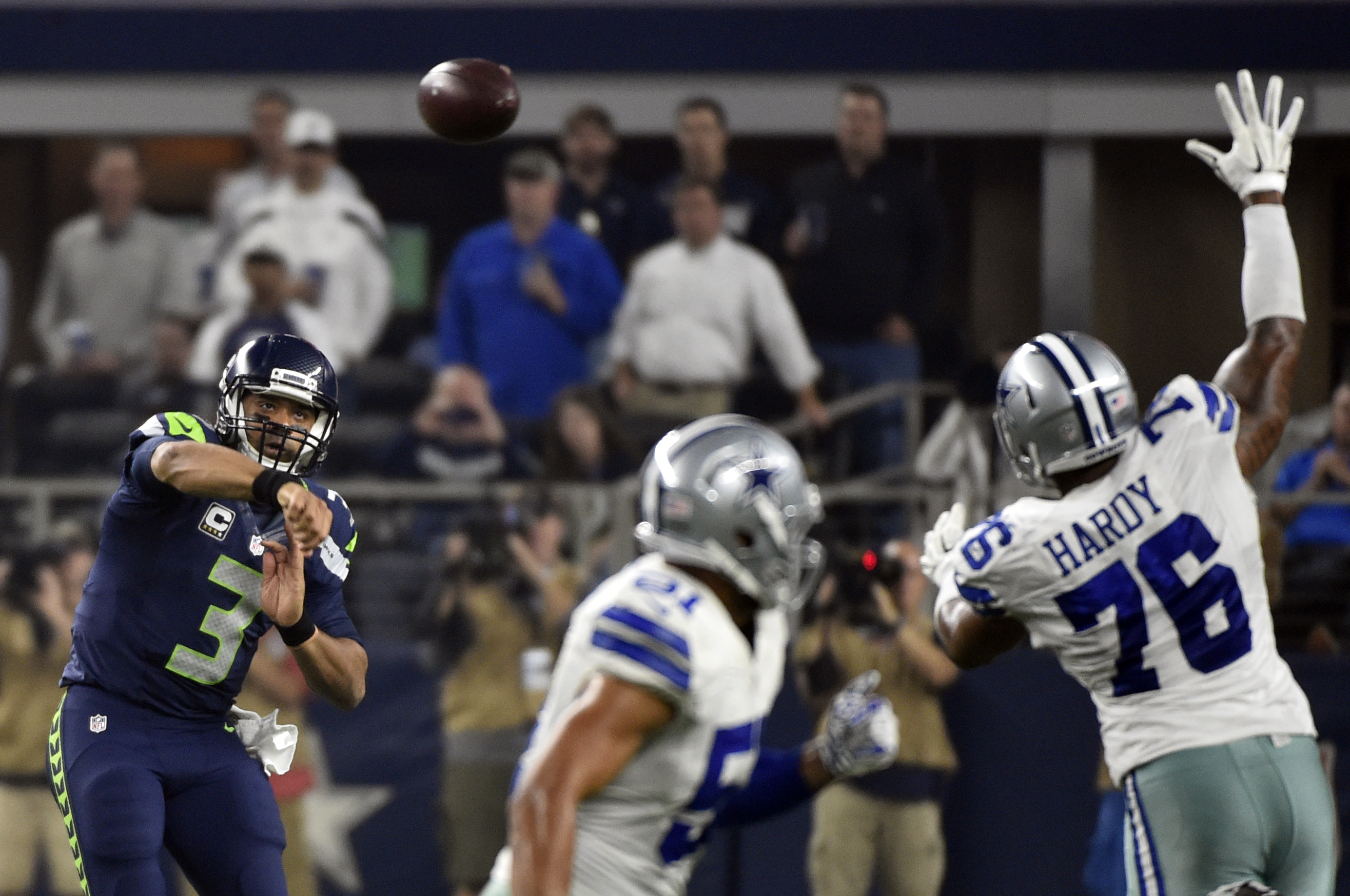 Seattle Seahawks' Russell Wilson (3) passes the ball past Dallas Cowboys' Greg Hardy (76) in the second half of an NFL football game Sunday, Nov. 1, 2015, in Arlington, Texas. (AP Photo/Michael Ainsworth)
