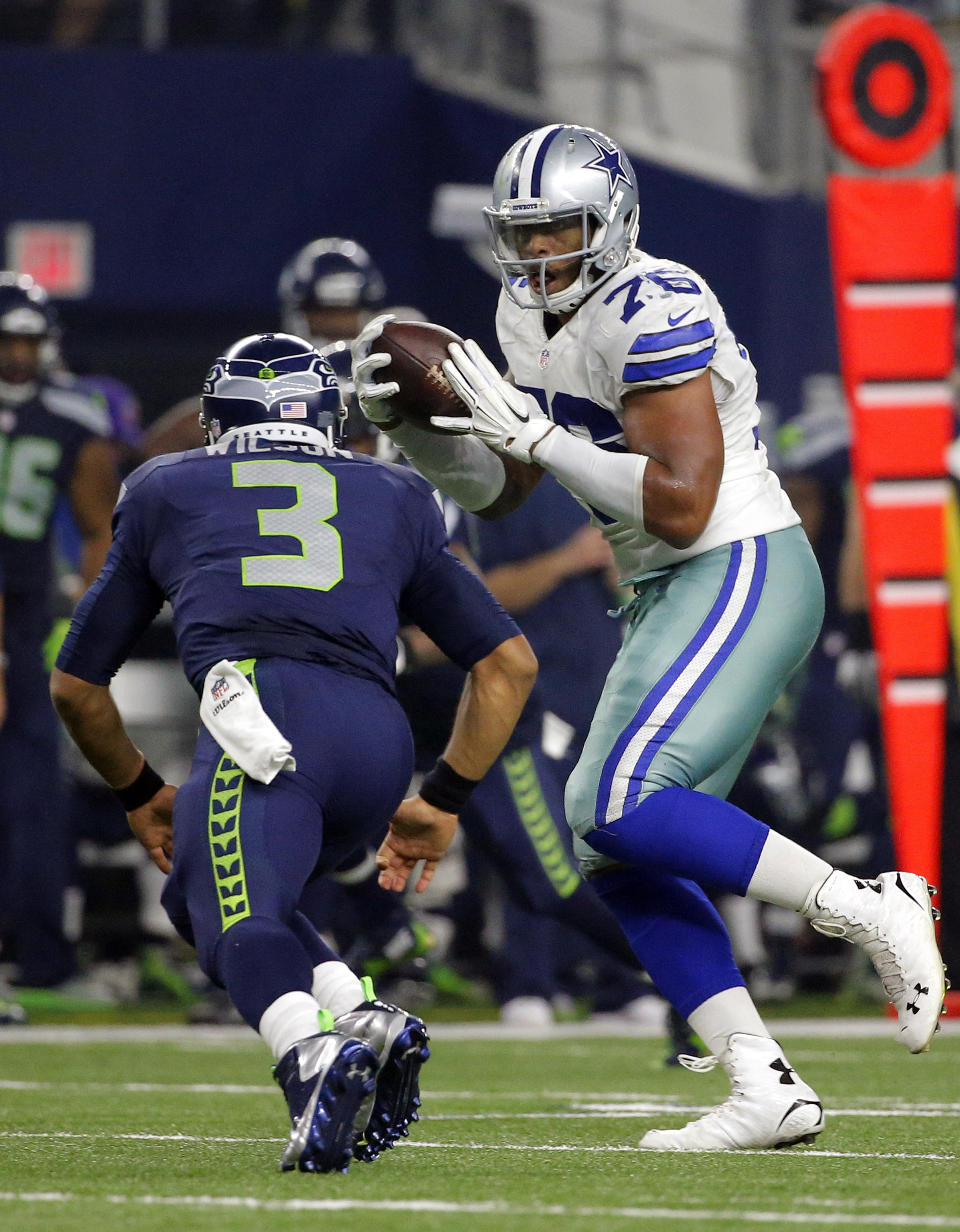 Seattle Seahawks quarterback Russell Wilson (3) runs to tackle Dallas Cowboys' Greg Hardy (76) who intercepted a pass from Wilson in the second half of an NFL football game Sunday, Nov. 1, 2015, in Arlington, Texas. (AP Photo/Brandon Wade)