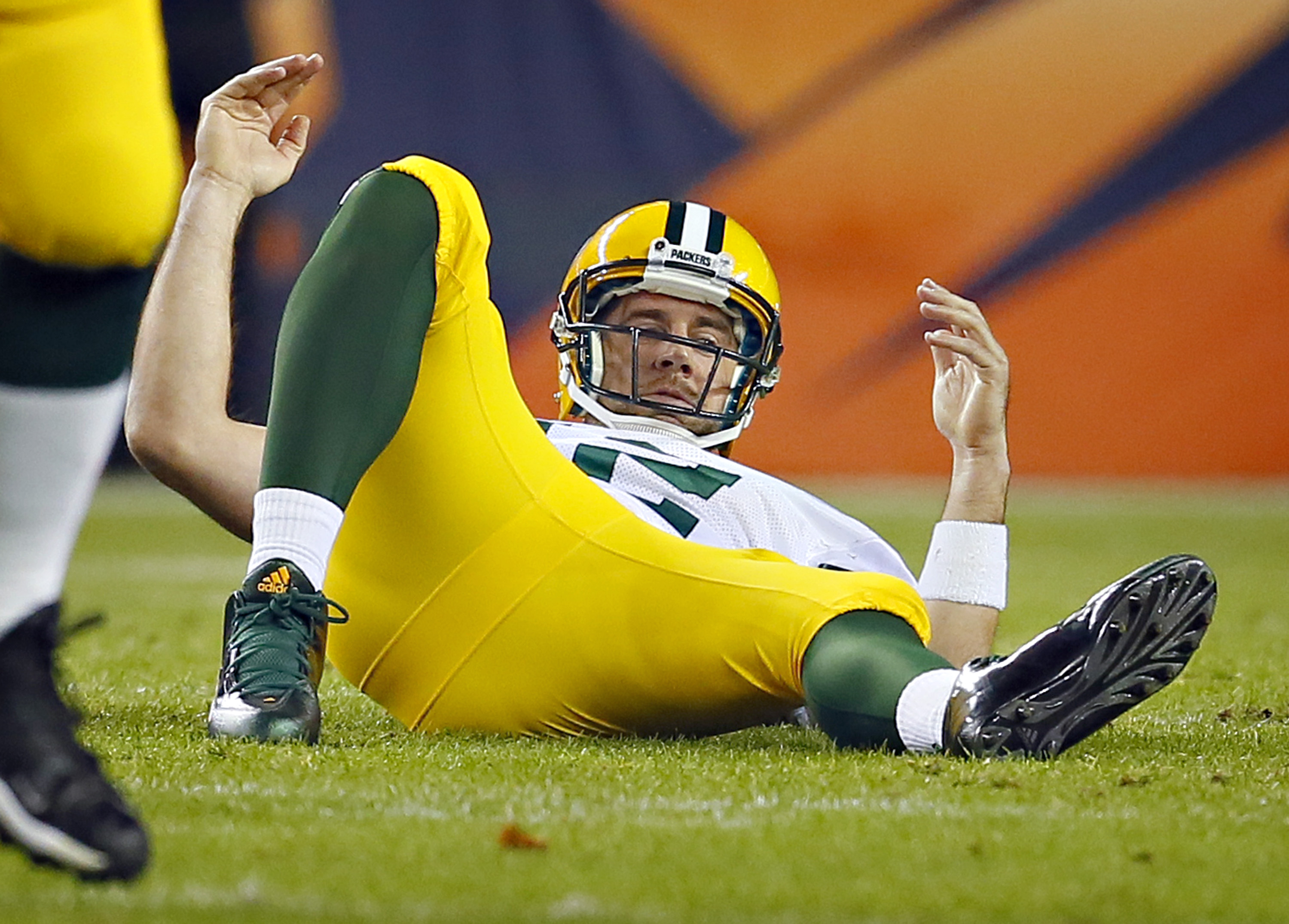 Green Bay Packers quarterback Aaron Rodgers (12) looks for a call as he lies on his back after a hit during the first half of an NFL football game against the Denver Broncos, Sunday, Nov. 1, 2015, in Denver. (AP Photo/Joe Mahoney)
