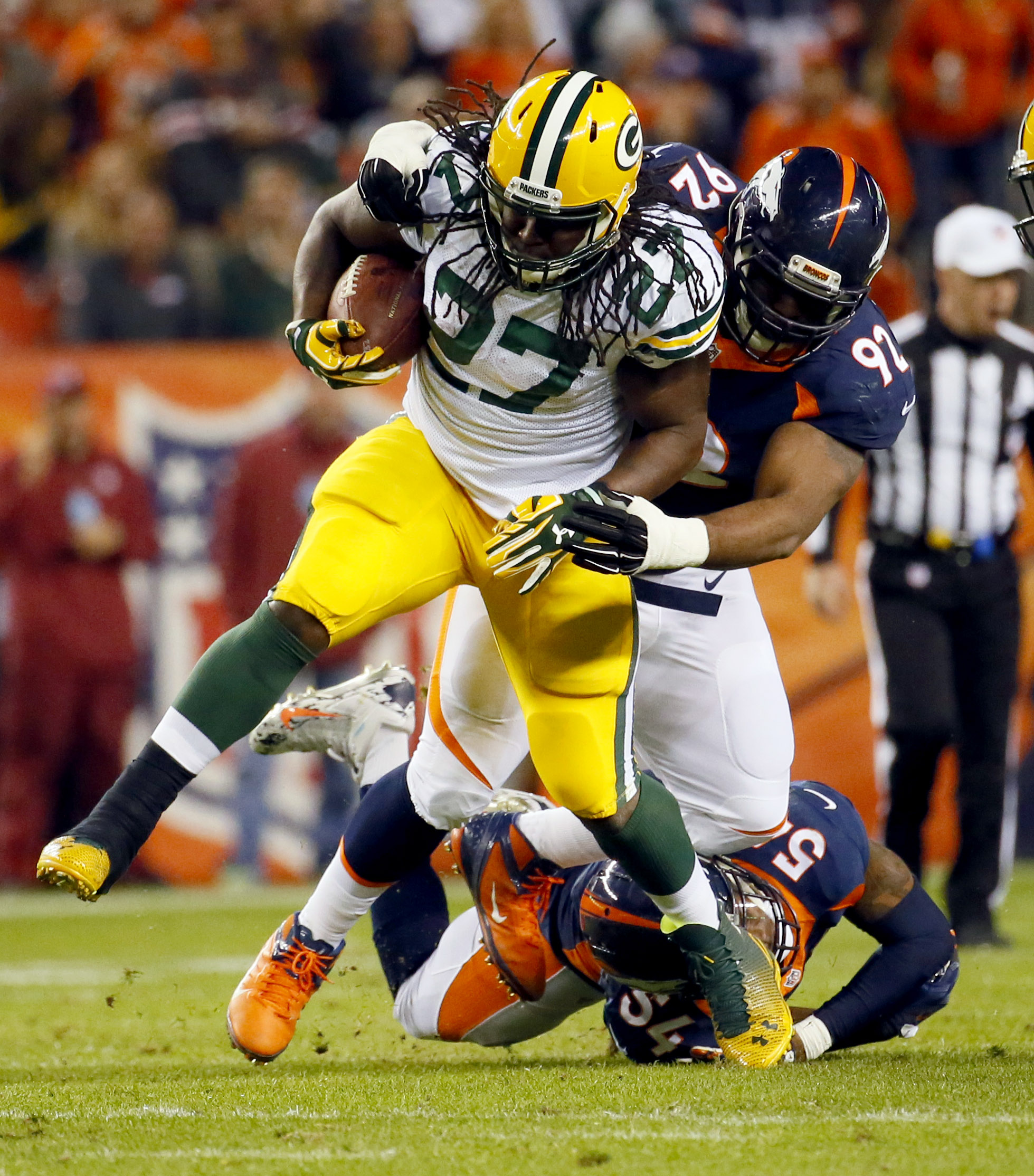 Green Bay Packers running back Eddie Lacy (27) is hit by Denver Broncos inside linebacker Brandon Marshall (54) and nose tackle Sylvester Williams (92) during the second half of an NFL football game, Sunday, Nov. 1, 2015, in Denver. (AP Photo/Jack Dempsey