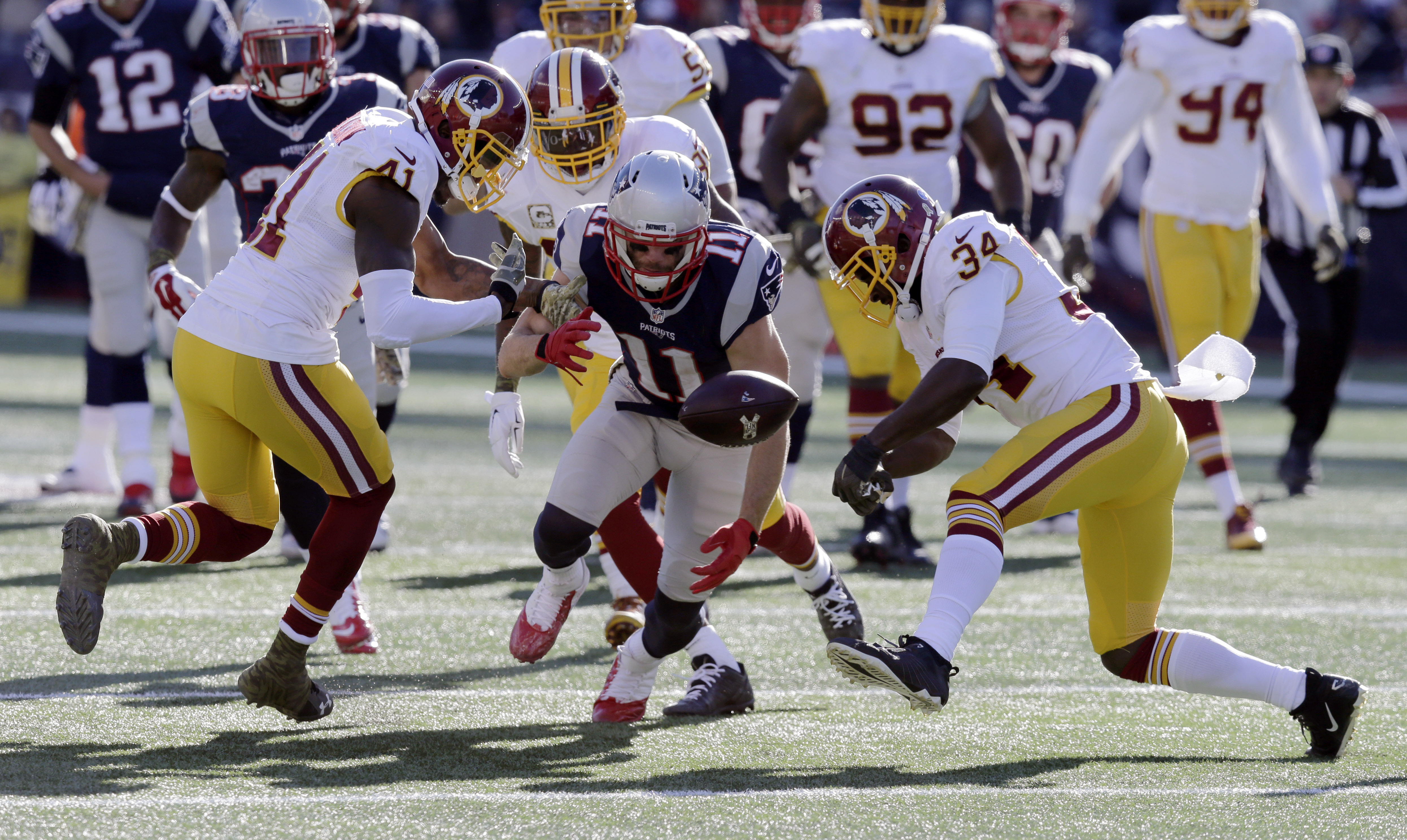 New England Patriots wide receiver Julian Edelman (11) fumbles between Washington Redskins defensive backs Will Blackmon (41) and Trenton Robinson (34) during the first half of an NFL football game, Sunday, Nov. 8, 2015, in Foxborough, Mass. Blackmon reco