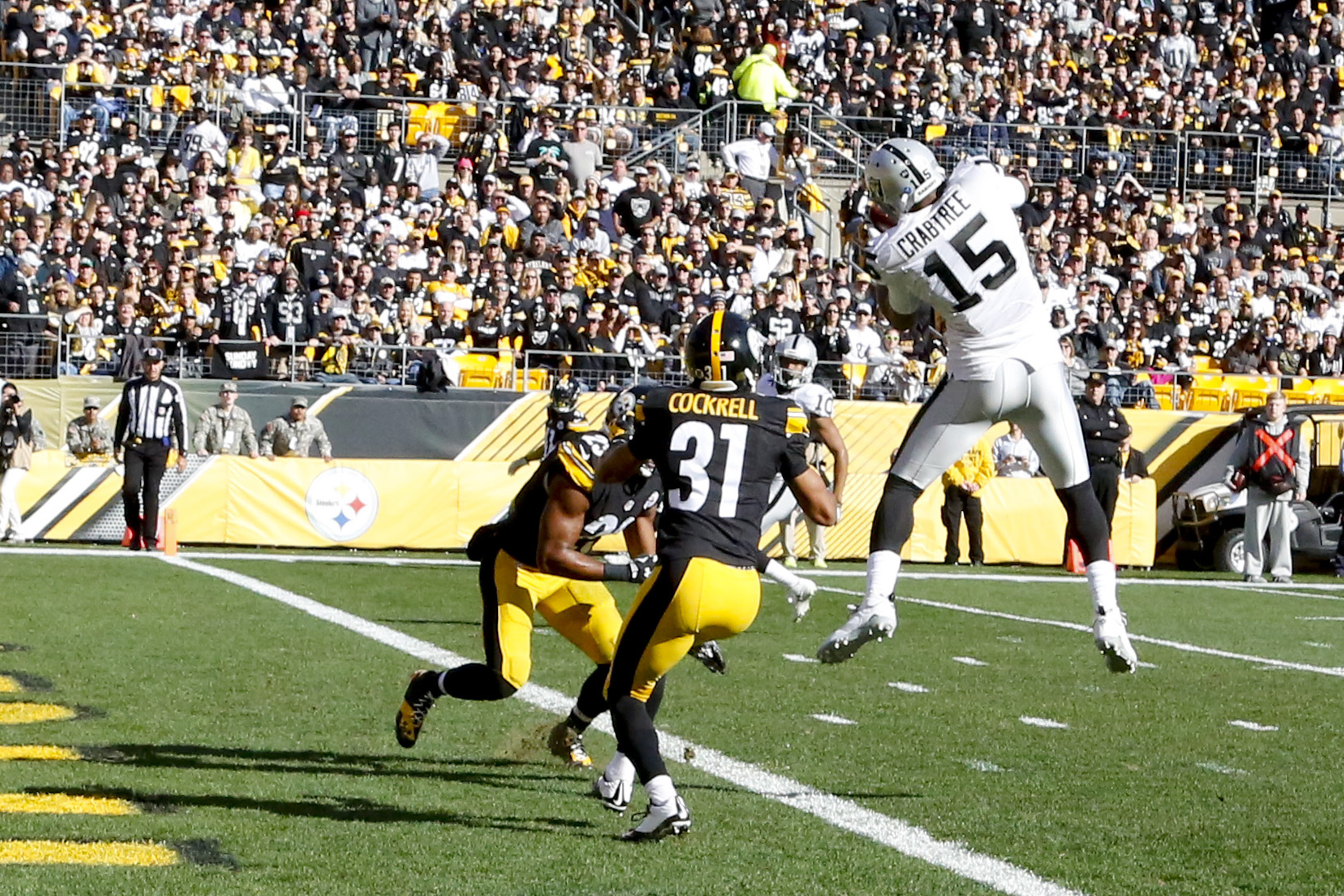 Oakland Raiders wide receiver Michael Crabtree (15) makes a touchdown catch in front of Pittsburgh Steelers defensive back Ross Cockrell (31) and free safety Mike Mitchell (23) in the first quarter of an NFL football game, Sunday, Nov. 8, 2015, in Pittsbu