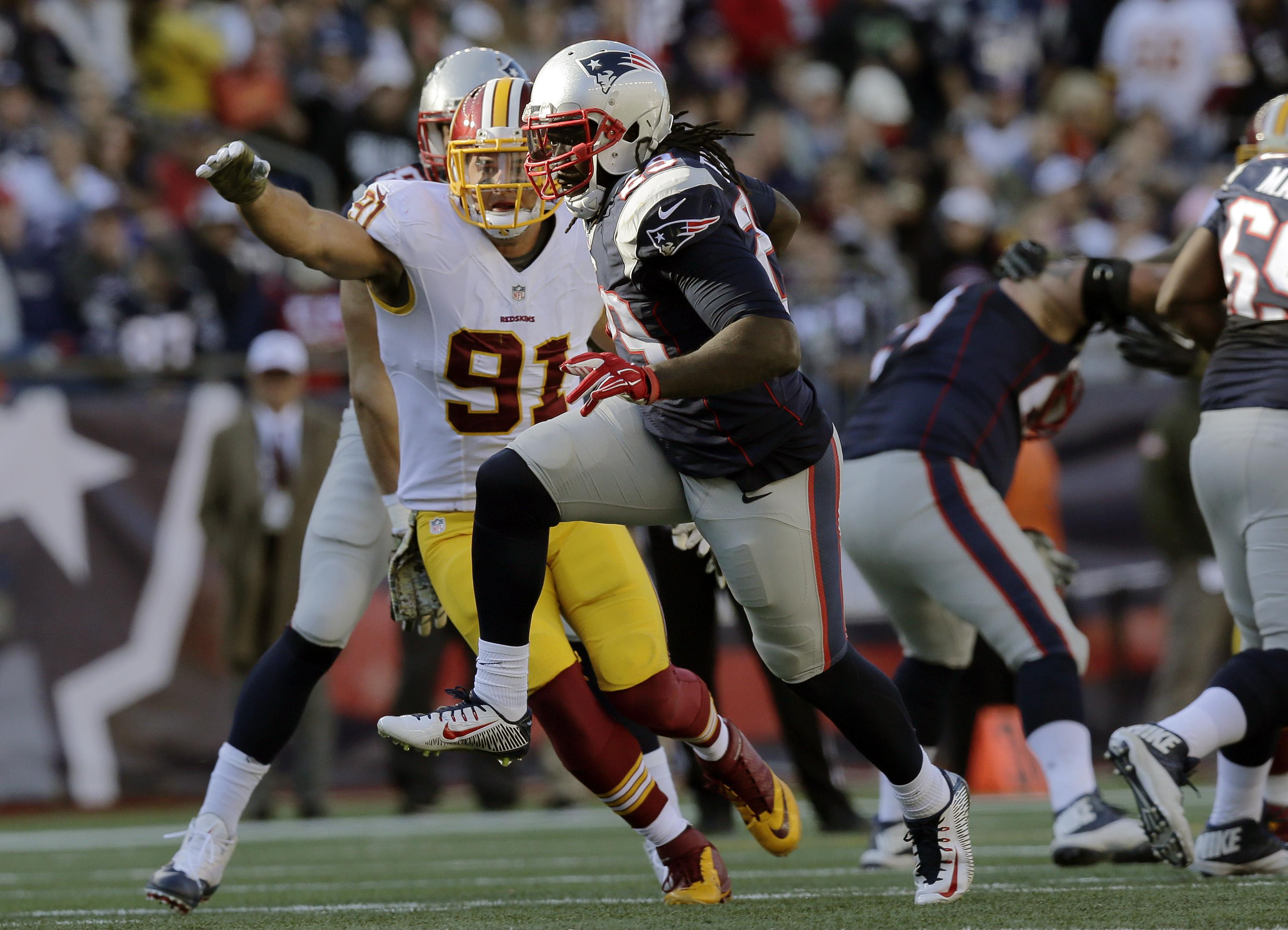 New England Patriots running back LeGarrette Blount (29) runs away from Washington Redskins linebacker Ryan Kerrigan (91) during the first half of an NFL football game, Sunday, Nov. 8, 2015, in Foxborough, Mass. (AP Photo/Charles Krupa)
