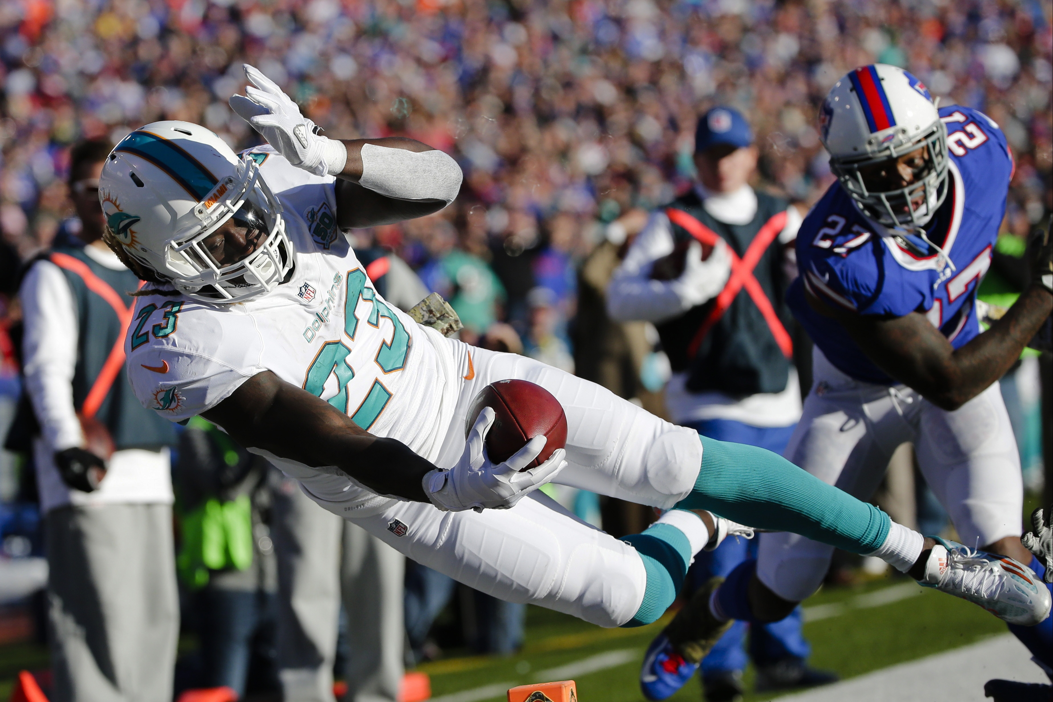 Miami Dolphins running back Jay Ajayi (23) dives past Buffalo Bills' Duke Williams (27) during the second half of an NFL football game Sunday, Nov. 8, 2015, in Orchard Park, N.Y. (AP Photo/Bill Wippert)