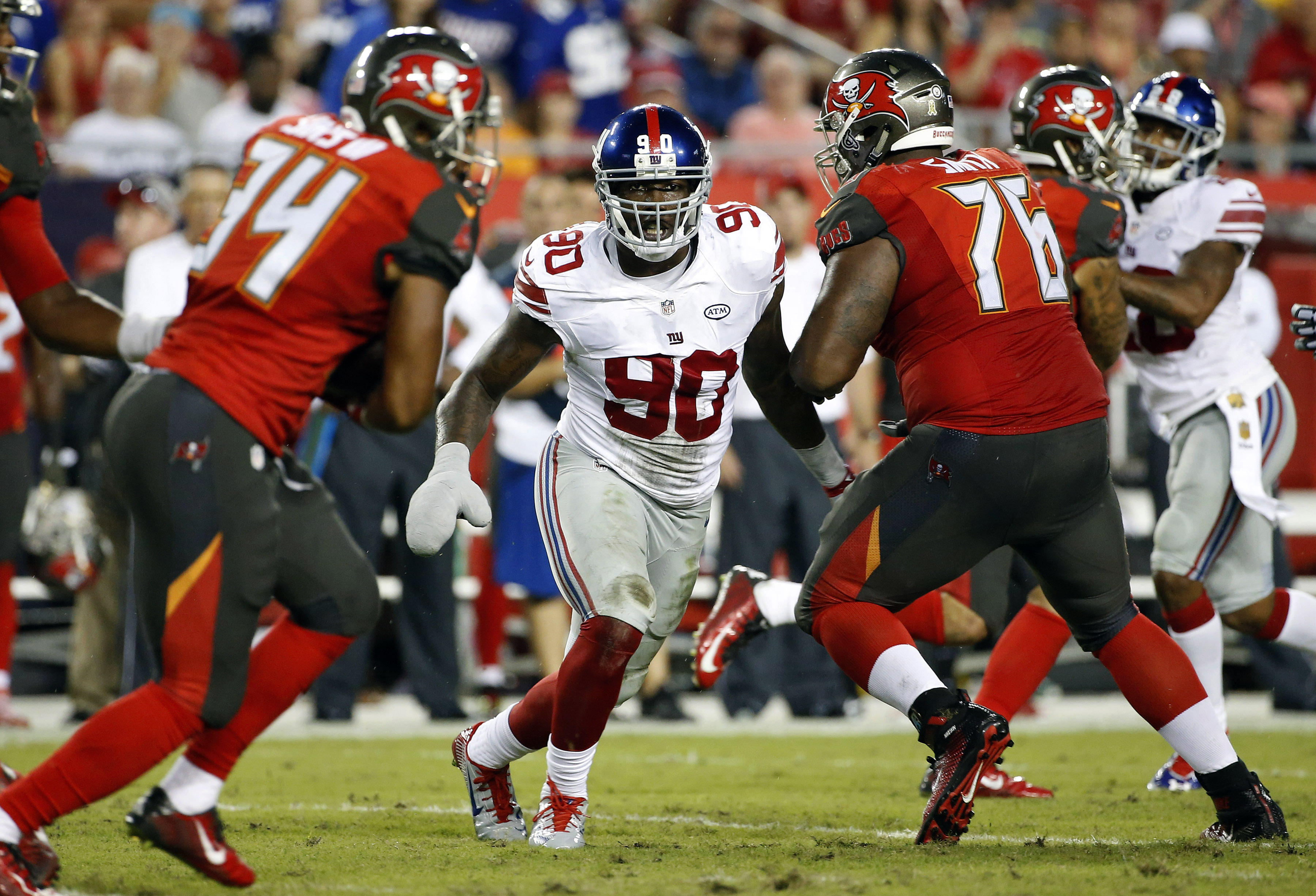 New York Giants defensive end Jason Pierre-Paul (90) slips between the Tampa Bay Buccaneers offense during the third quarter of an NFL football game Sunday, Nov. 8, 2015, in Tampa, Fla. Pierre-Paul is playing in his first game since damaging his hand in a