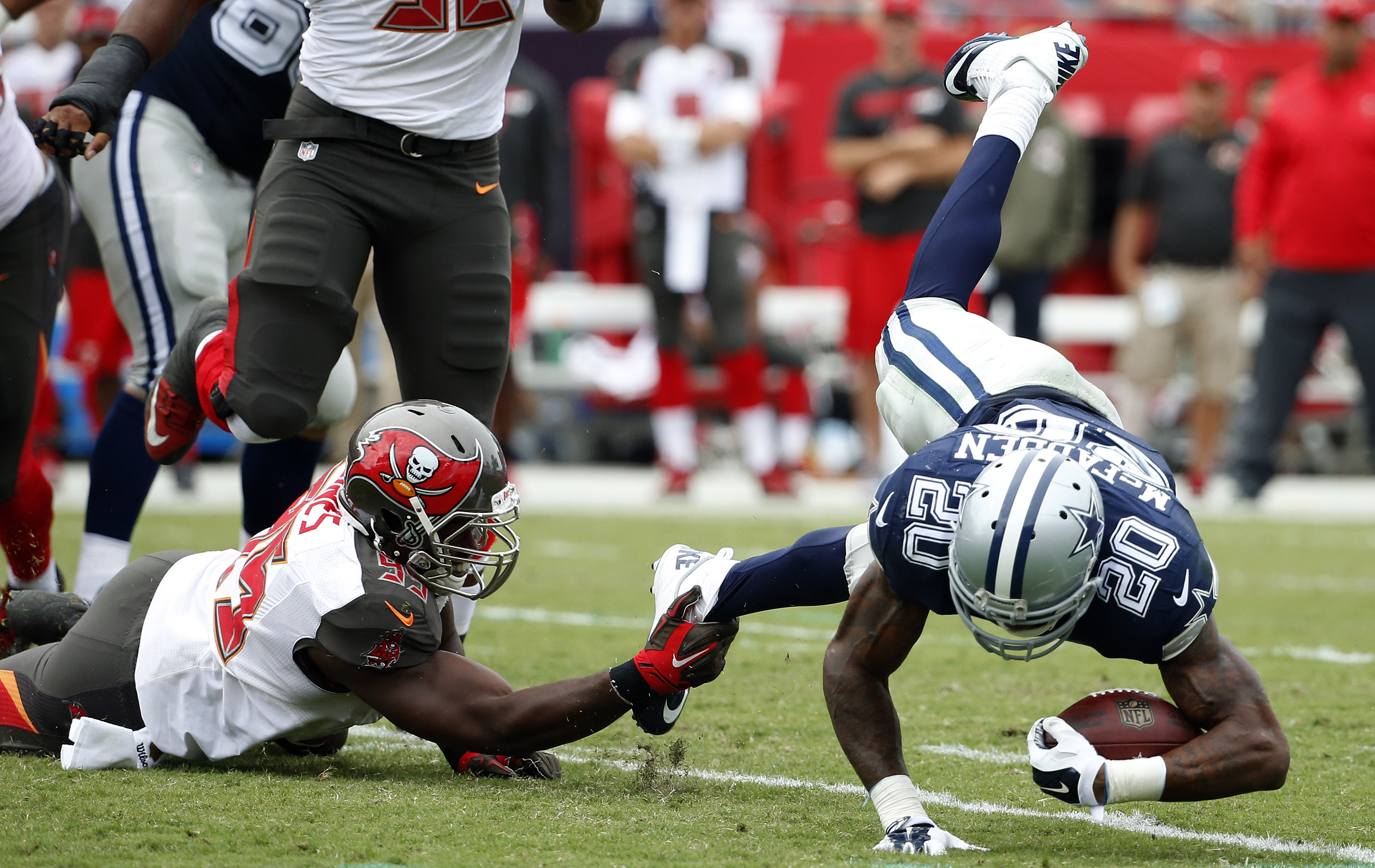 Dallas Cowboys running back Darren McFadden (20) gets tripped up by Tampa Bay Buccaneers defensive end Howard Jones (95) during the second quarter of an NFL football game Sunday, Nov. 15, 2015, in Tampa, Fla. (AP Photo/Brian Blanco)