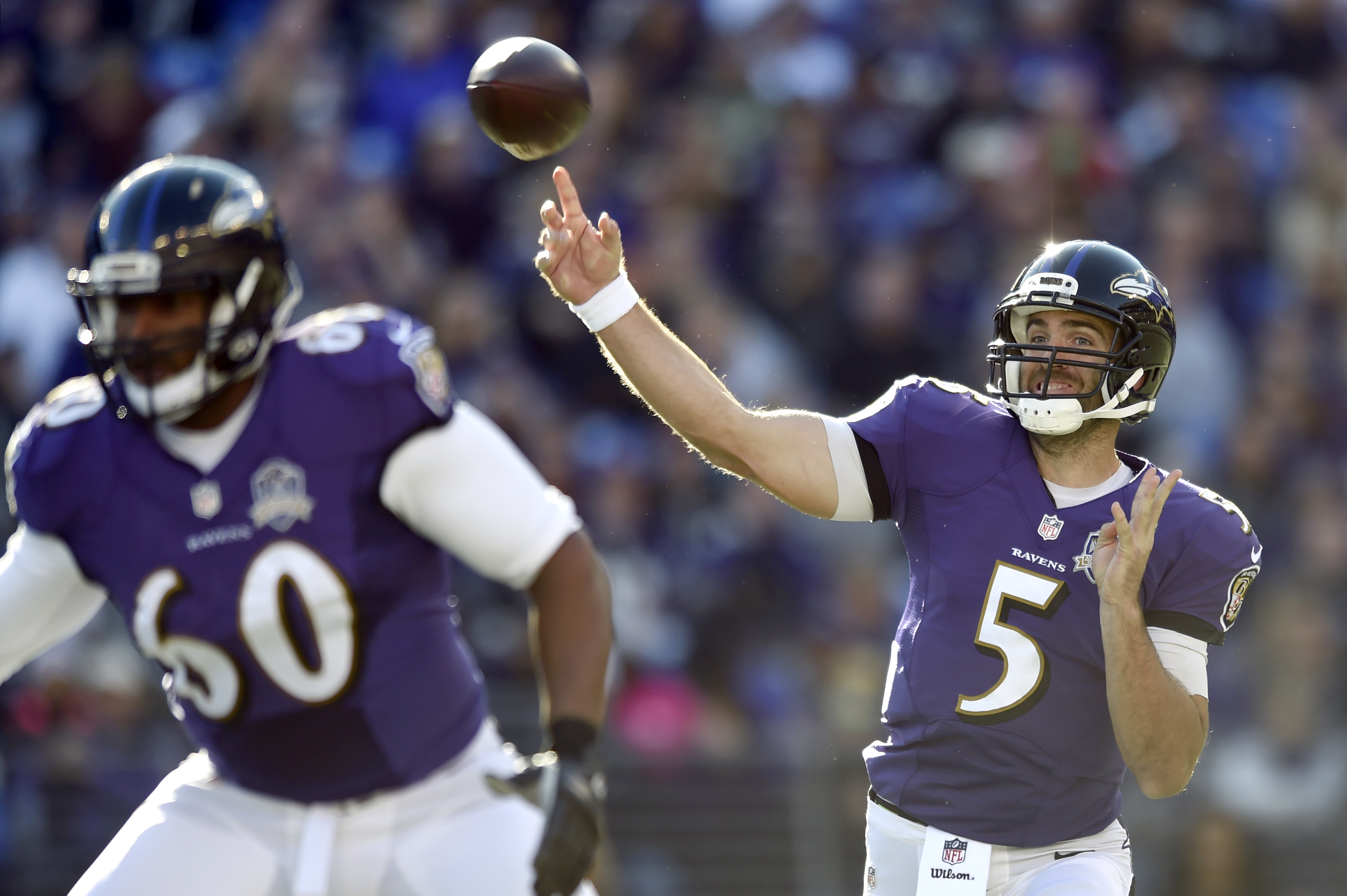 Baltimore Ravens quarterback Joe Flacco (5) throws to a receiver as he is protected by tackle Eugene Monroe in the first half an NFL football game against the Jacksonville Jaguars, Sunday, Nov. 15, 2015, in Baltimore. (AP Photo/Gail Burton)