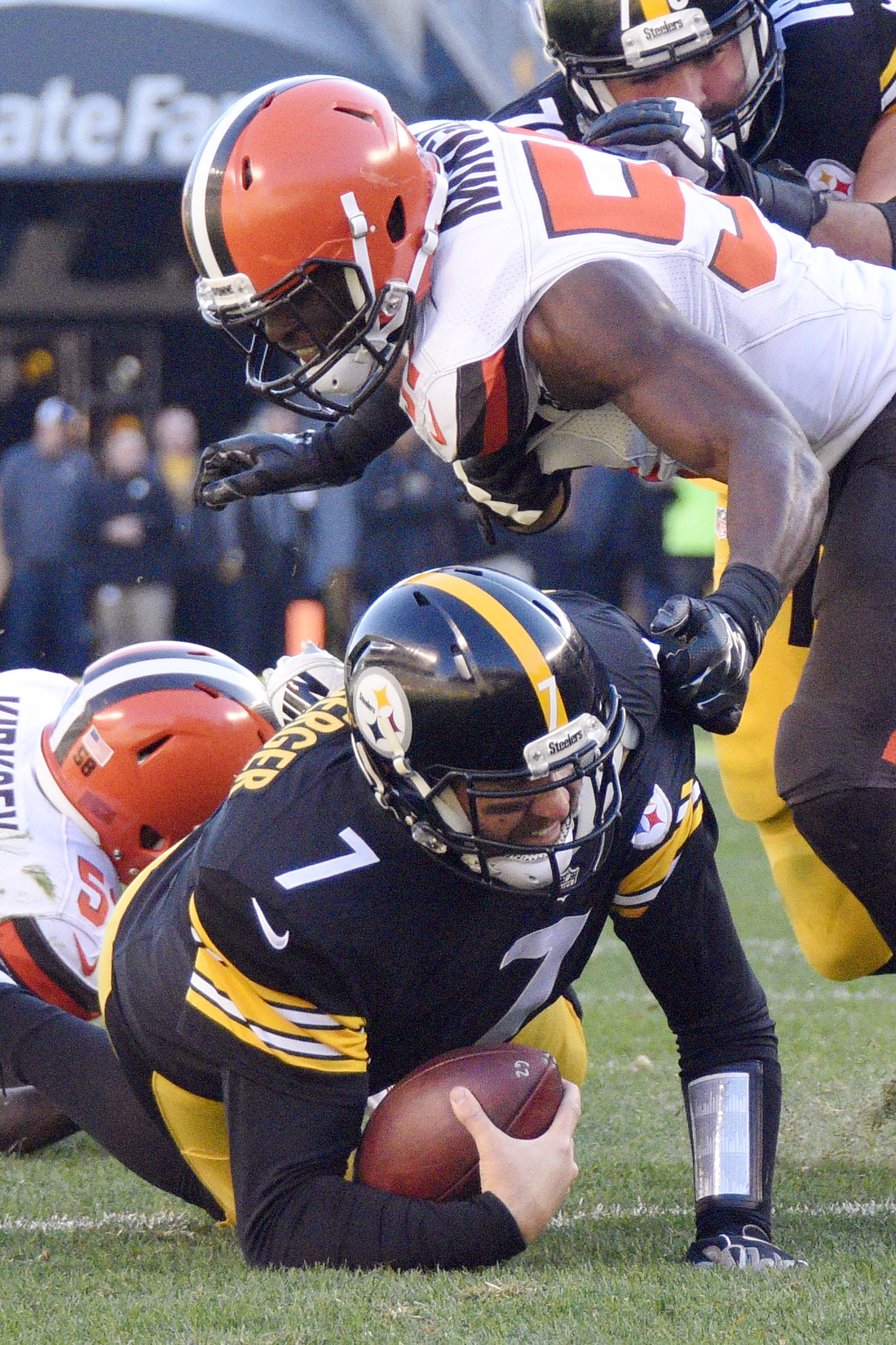 Pittsburgh Steelers quarterback Ben Roethlisberger (7) is tackled by Cleveland Browns inside linebacker Chris Kirksey (58) and outside linebacker Barkevious Mingo (51) as he scrambles in the second quarter of an NFL football game, Sunday, Nov. 15, 2015, i
