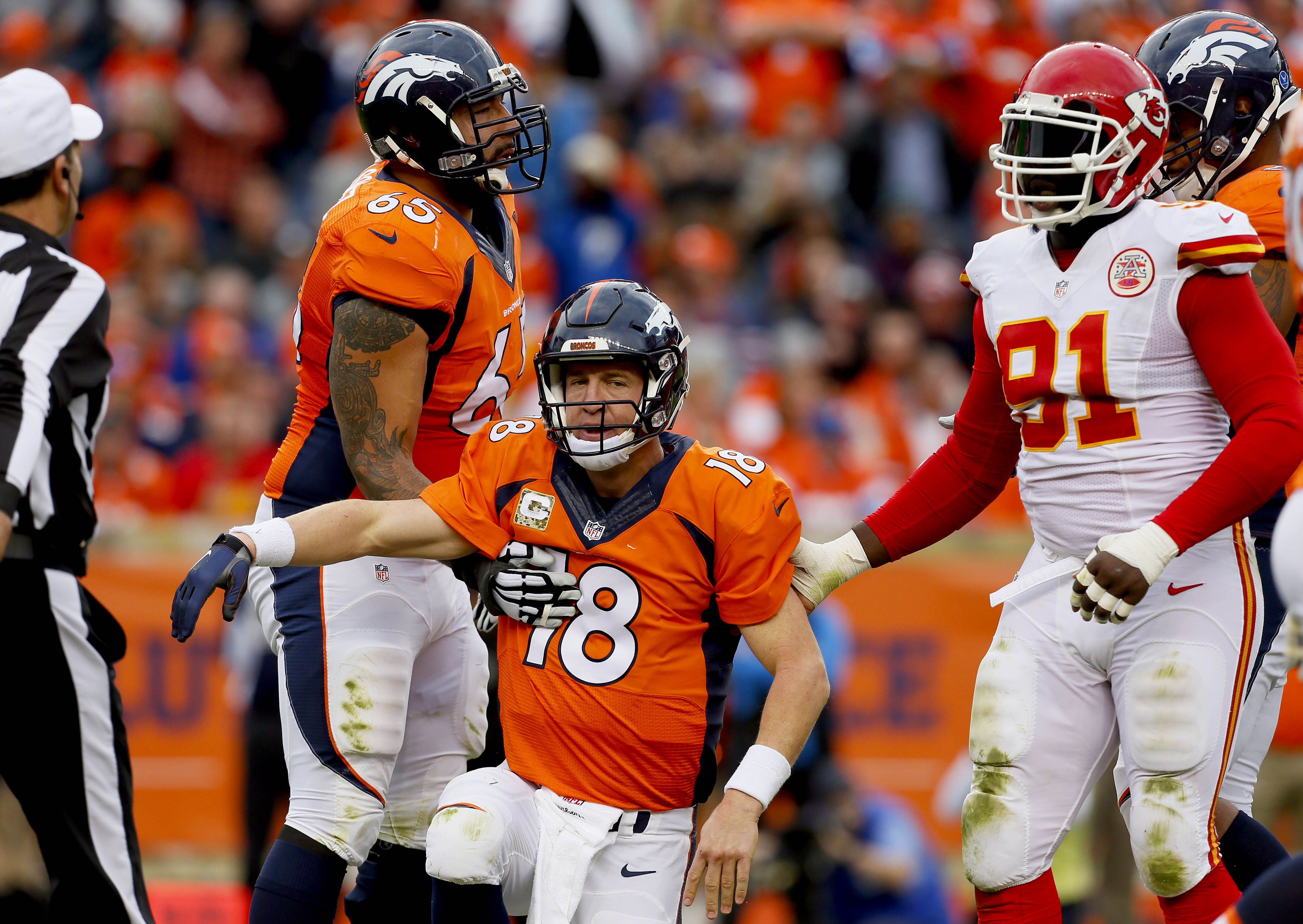 Denver Broncos quarterback Peyton Manning (18) is helped up to his feet by teammate Louis Vasquez (65) and Kansas City Chiefs outside linebacker Tamba Hali (91)after a sack during the first half of an NFL football game, Sunday, Nov. 15, 2015, in Denver. (