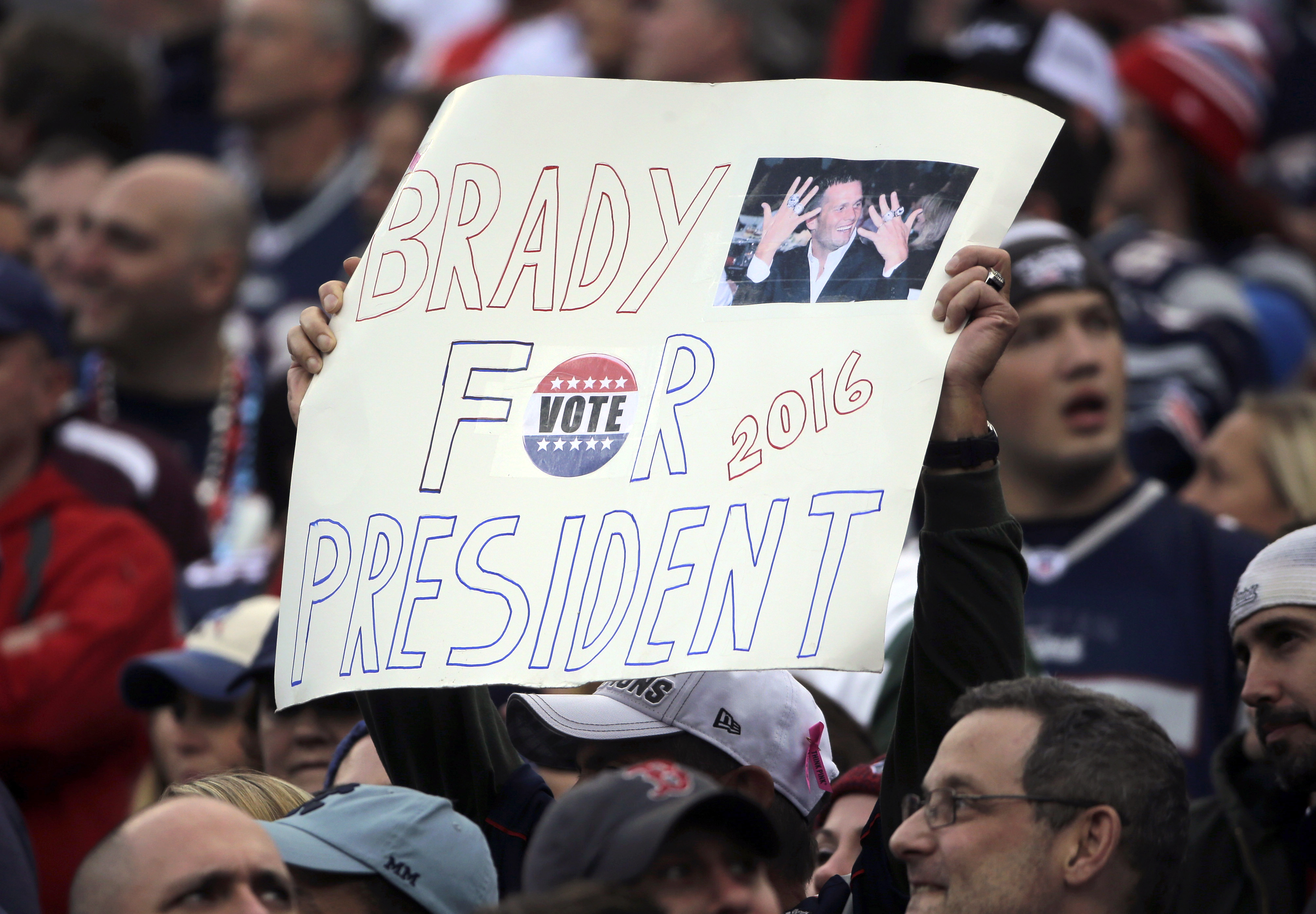 FILE - In this Oct. 25, 2015 file photo, a New England Patriots fan holds a sign that supports Patriots quarterback Tom Brady for president during an NFL football game against the New York Jets in Foxborough, Mass. GQ magazine asked Brady, its 2015 Man of