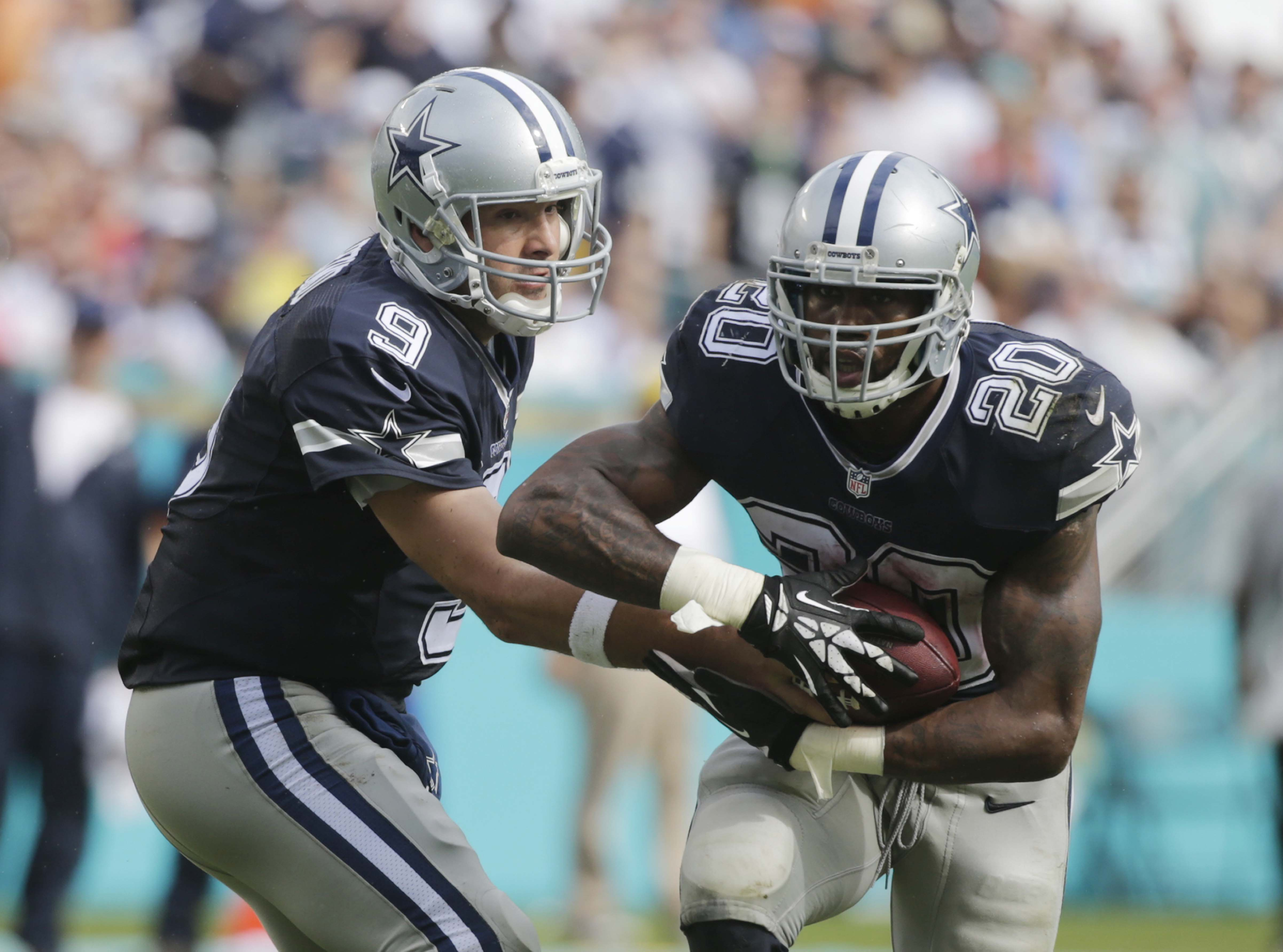 Dallas Cowboys quarterback Tony Romo (9) hands the ball to running back Darren McFadden (20) during the first half of an NFL football game against the Miami Dolphins, Sunday, Nov. 22, 2015, in Miami Gardens, Fla. (AP Photo/Wilfredo Lee)