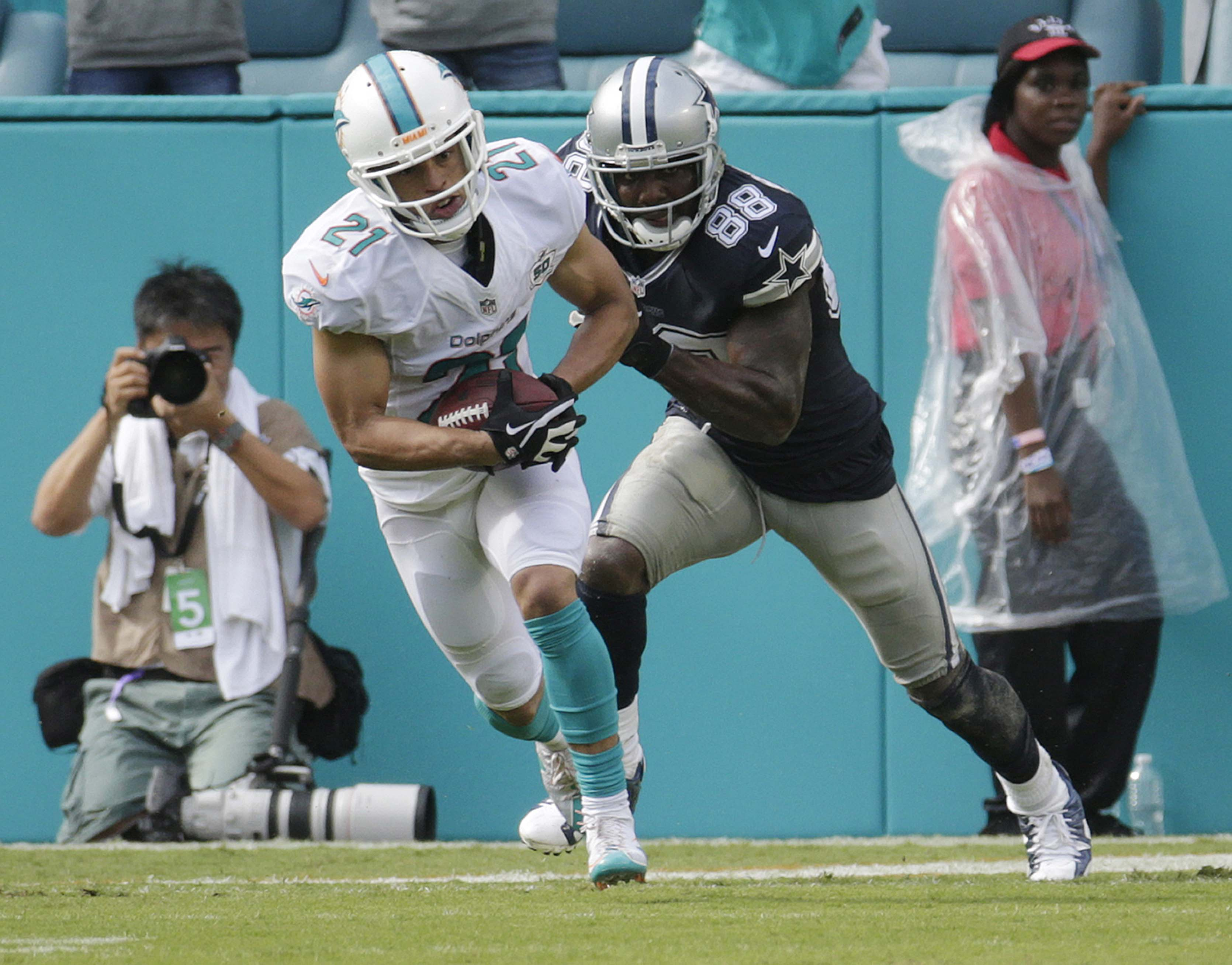 Miami Dolphins cornerback Brent Grimes (21) intercepts the ball as Dallas Cowboys wide receiver Dez Bryant (88) attempts top tackle during the first half of an NFL football game, Sunday, Nov. 22, 2015, in Miami Gardens, Fla.  (AP Photo/Lynne Sladky)