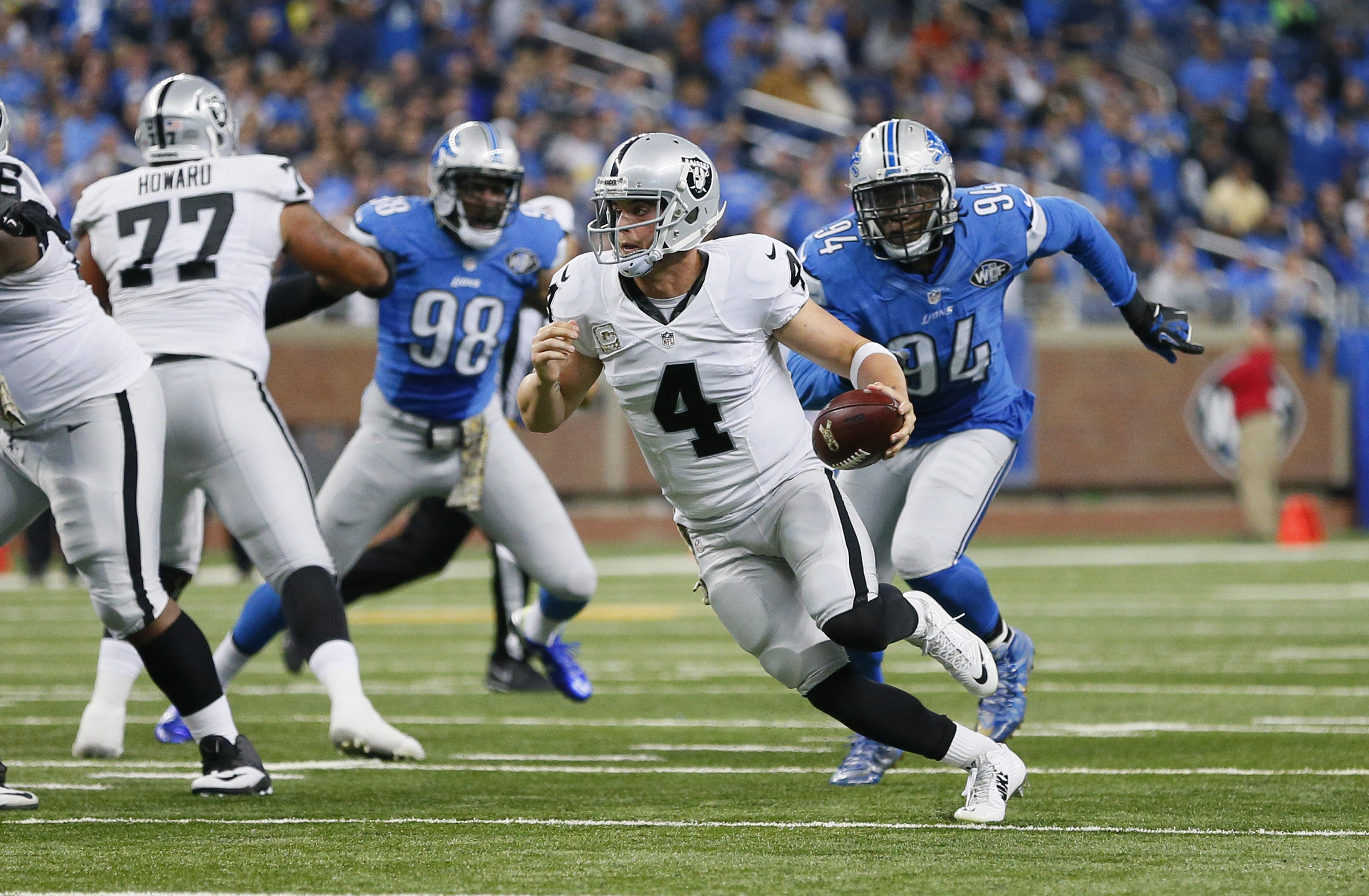 Oakland Raiders quarterback Derek Carr (4) scrambles for yardage while chased by Detroit Lions defensive end Ezekiel Ansah (94) during the second half of an NFL football game, Sunday, Nov. 22, 2015, in Detroit. (AP Photo/Rick Osentoski)