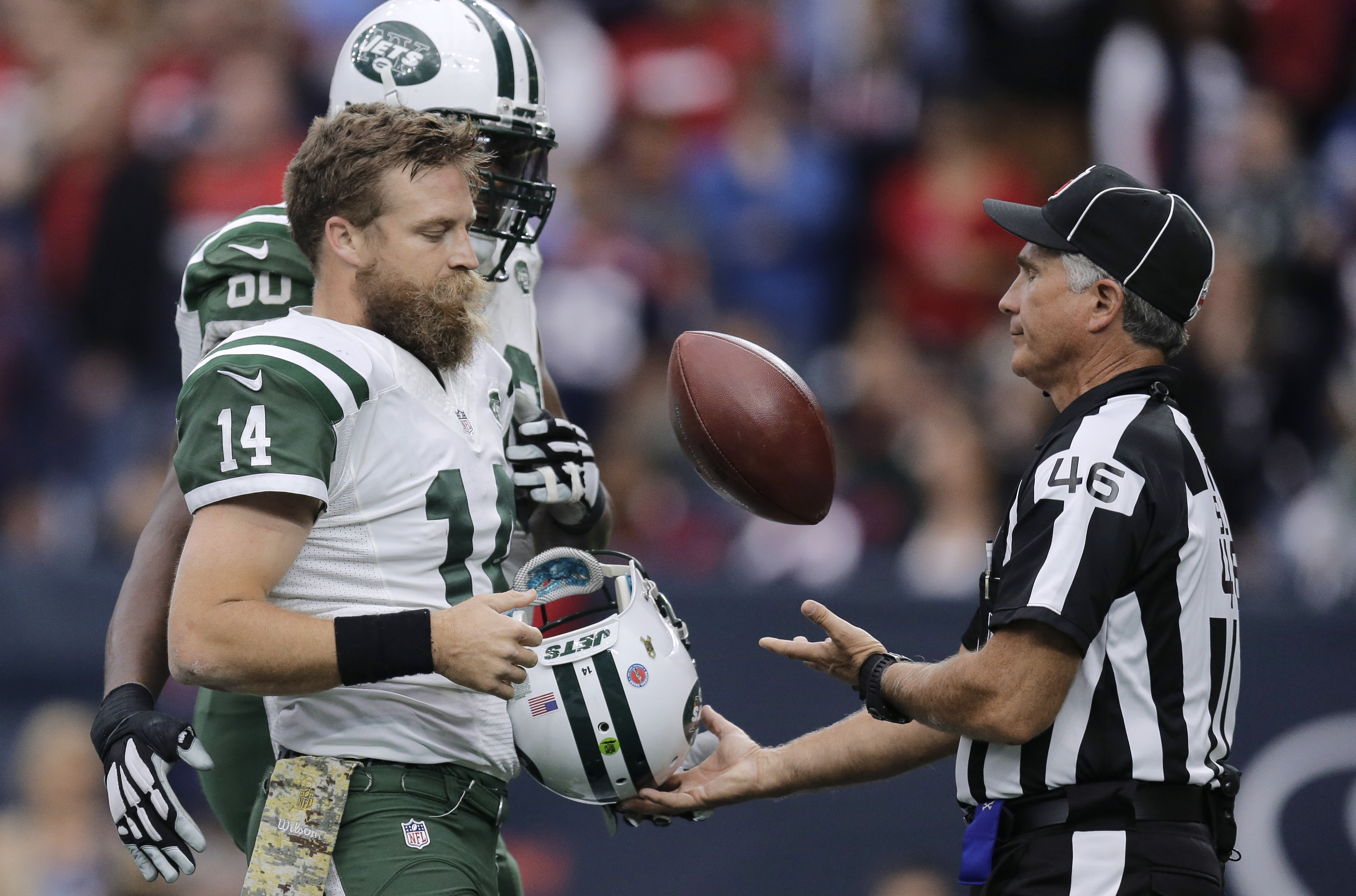 New York Jets quarterback Ryan Fitzpatrick (14) trades official Perry Paganelli (46) the ball for his helmet after he scored a touchdown against the Houston Texans during the second half of an NFL football game, Sunday, Nov. 22, 2015, in Houston. Fitzpatr