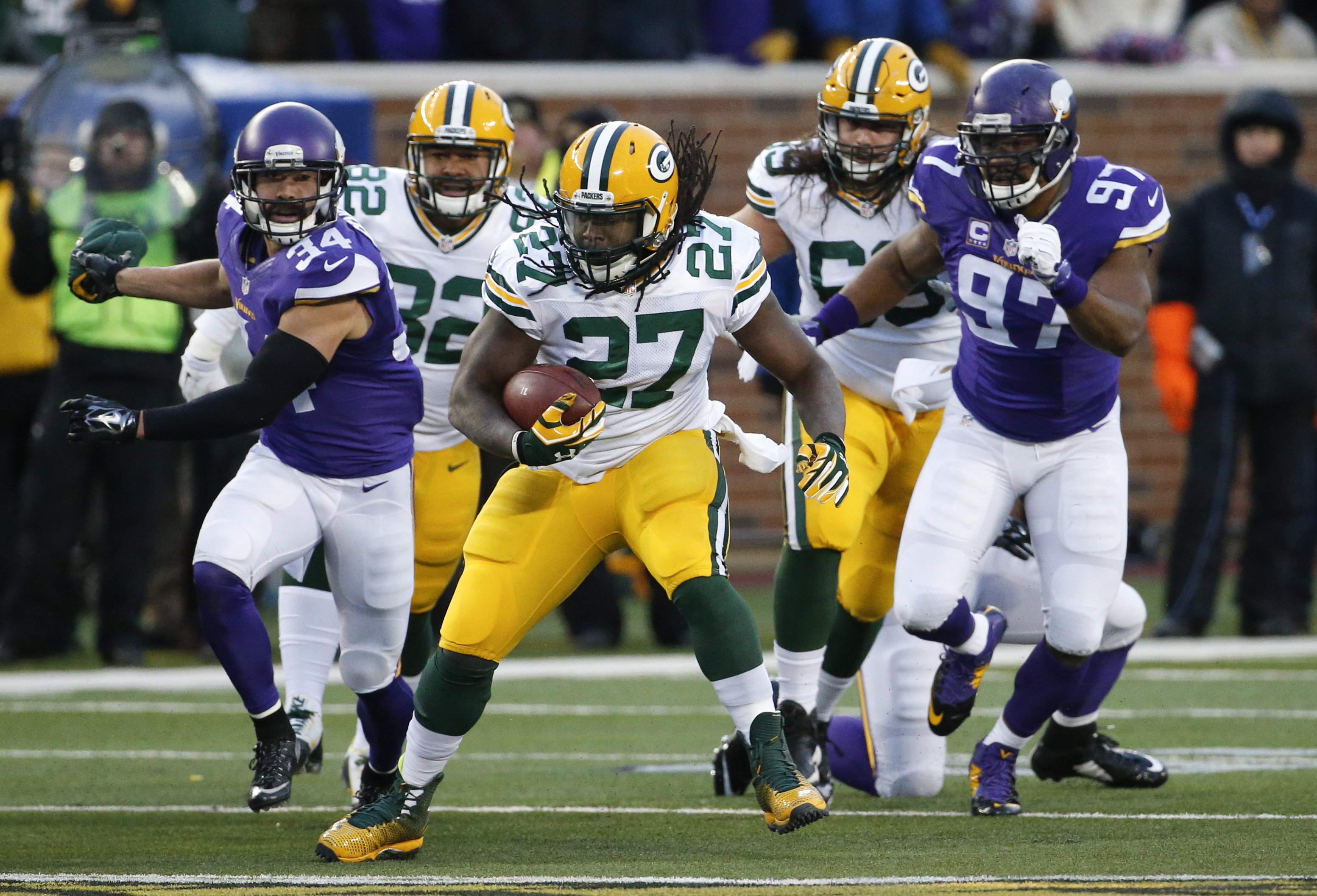 Green Bay Packers running back Eddie Lacy (27) runs past Minnesota Vikings strong safety Andrew Sendejo (34) an defensive end Everson Griffen (97) during the first half of an NFL football game in Minneapolis, Sunday, Nov. 22, 2015. (AP Photo/Ann Heisenfel