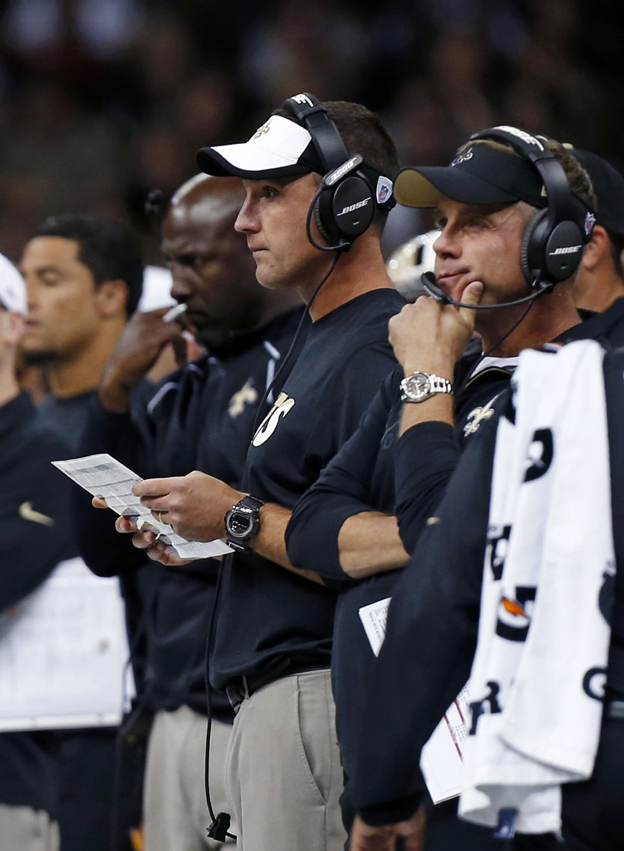 In this Aug. 30, 2015,  photo, New Orleans Saints then-senior defensive assistant Dennis Allen, center, and head coach Sean Payton, right, watch from the sideline in the first half of an NFL preseason football game against the Houston Texans in New Orlean