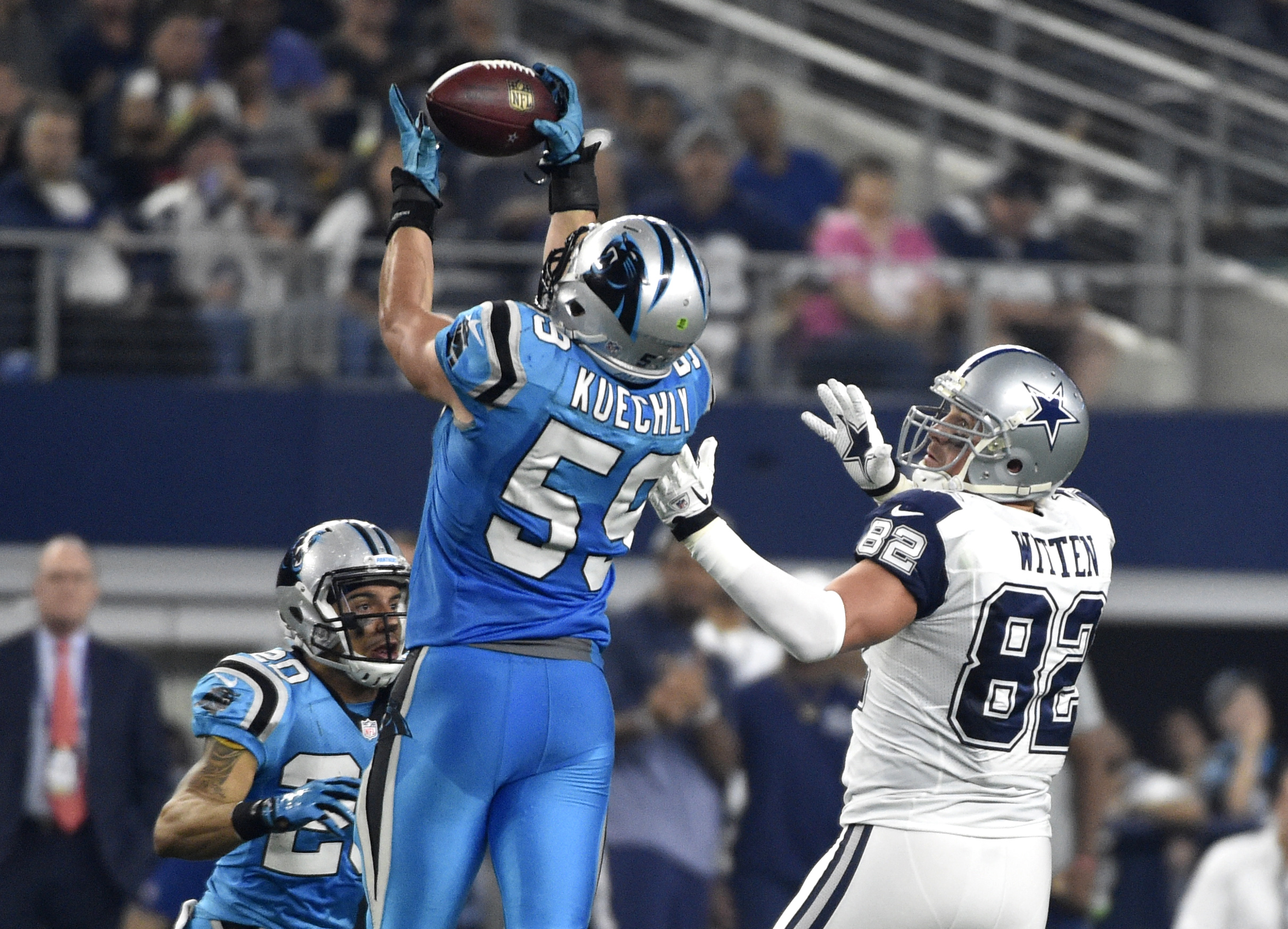 Carolina Panthers middle linebacker Luke Kuechly (59) intercepts a pass intended for Dallas Cowboys tight end Jason Witten (82) as Kurt Coleman (20) watches during the first half of an NFL football game, Thursday Nov. 26, 2015, in Arlington, Texas. Kuechl