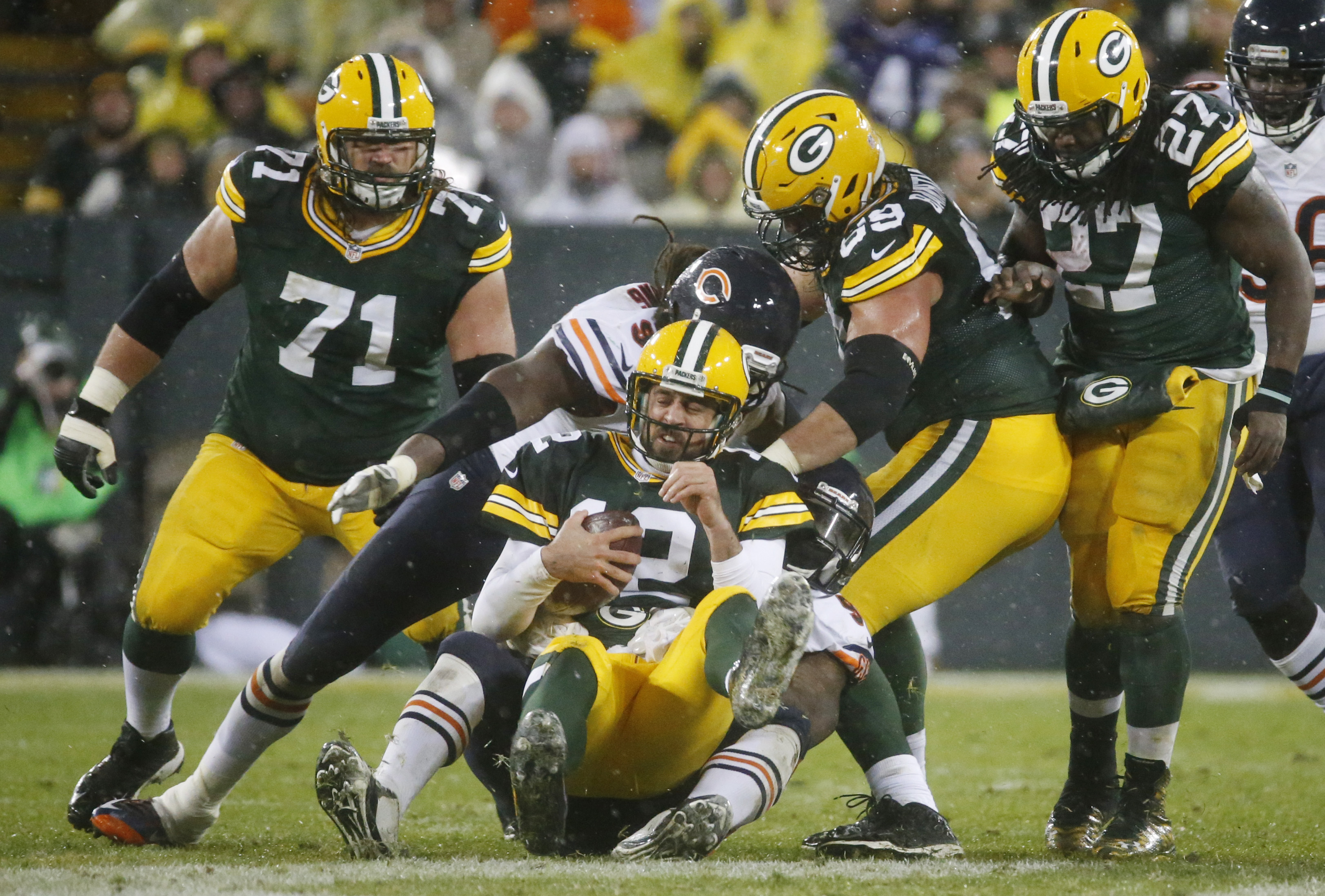Green Bay Packers' Aaron Rodgers grimaces as he is tackled after recovering a fumble during the second half of an NFL football game against the Chicago Bears Thursday, Nov. 26, 2015, in Green Bay, Wis. (AP Photo/Mike Roemer)