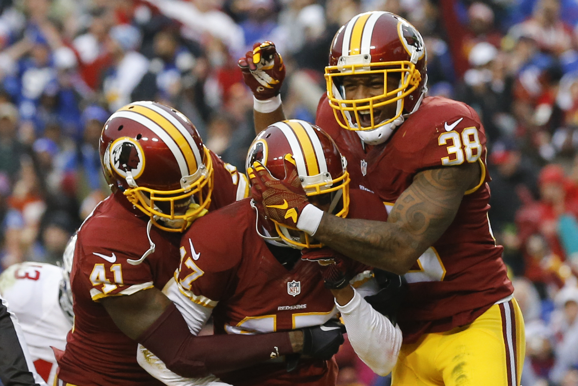Washington Redskins cornerback Quinton Dunbar, center, is mobbed by his teammates cornerback Will Blackmon (41) and free safety Dashon Goldson (38) after he intercepted a pass in the end zone intended for New York Giants wide receiver Rueben Randle during