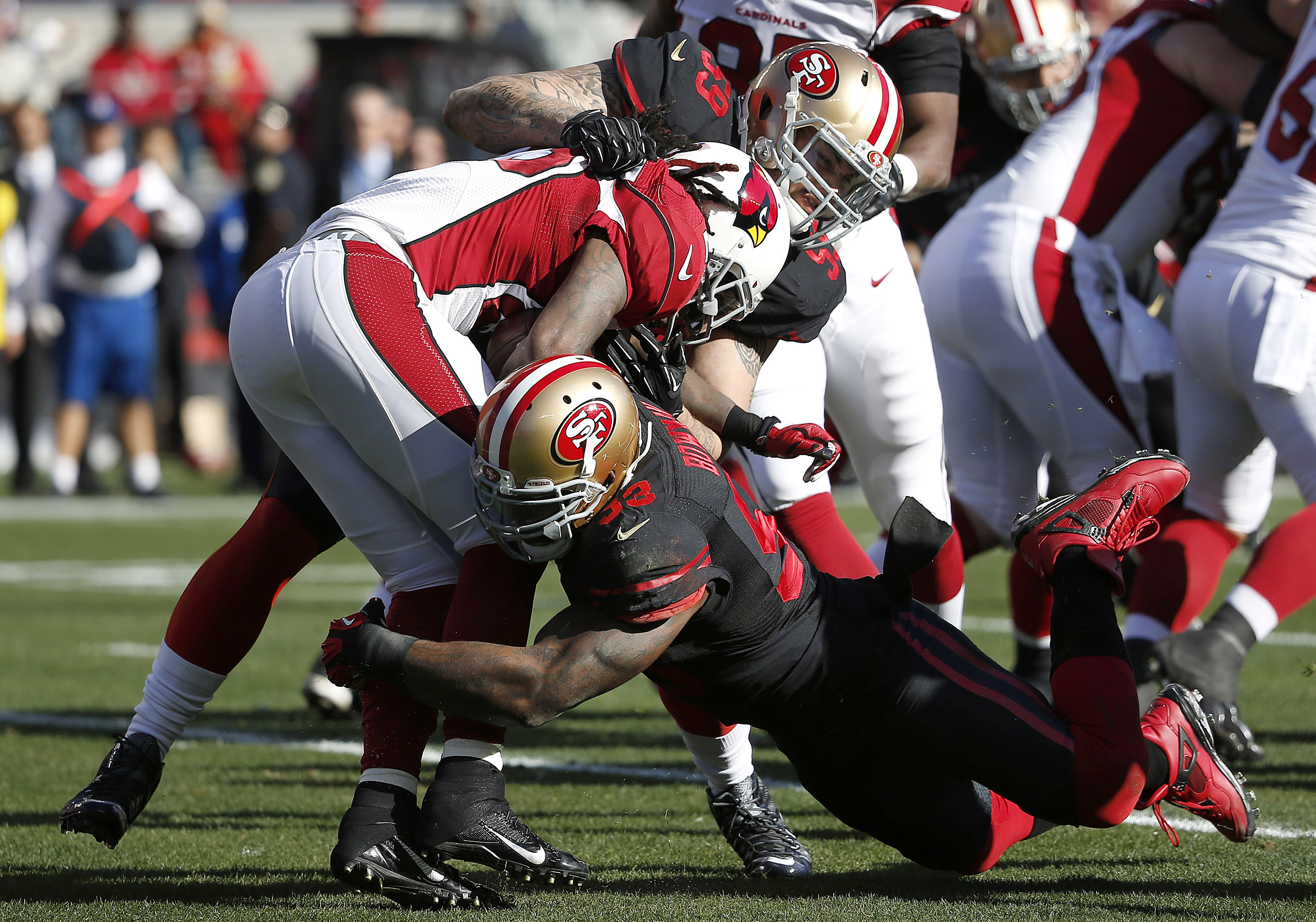 Arizona Cardinals running back Chris Johnson, center, is tackled by San Francisco 49ers linebacker Aaron Lynch (59) and linebacker NaVorro Bowman (53) during the first half of an NFL football game in Santa Clara, Calif., Sunday, Nov. 29, 2015. (AP Photo/T
