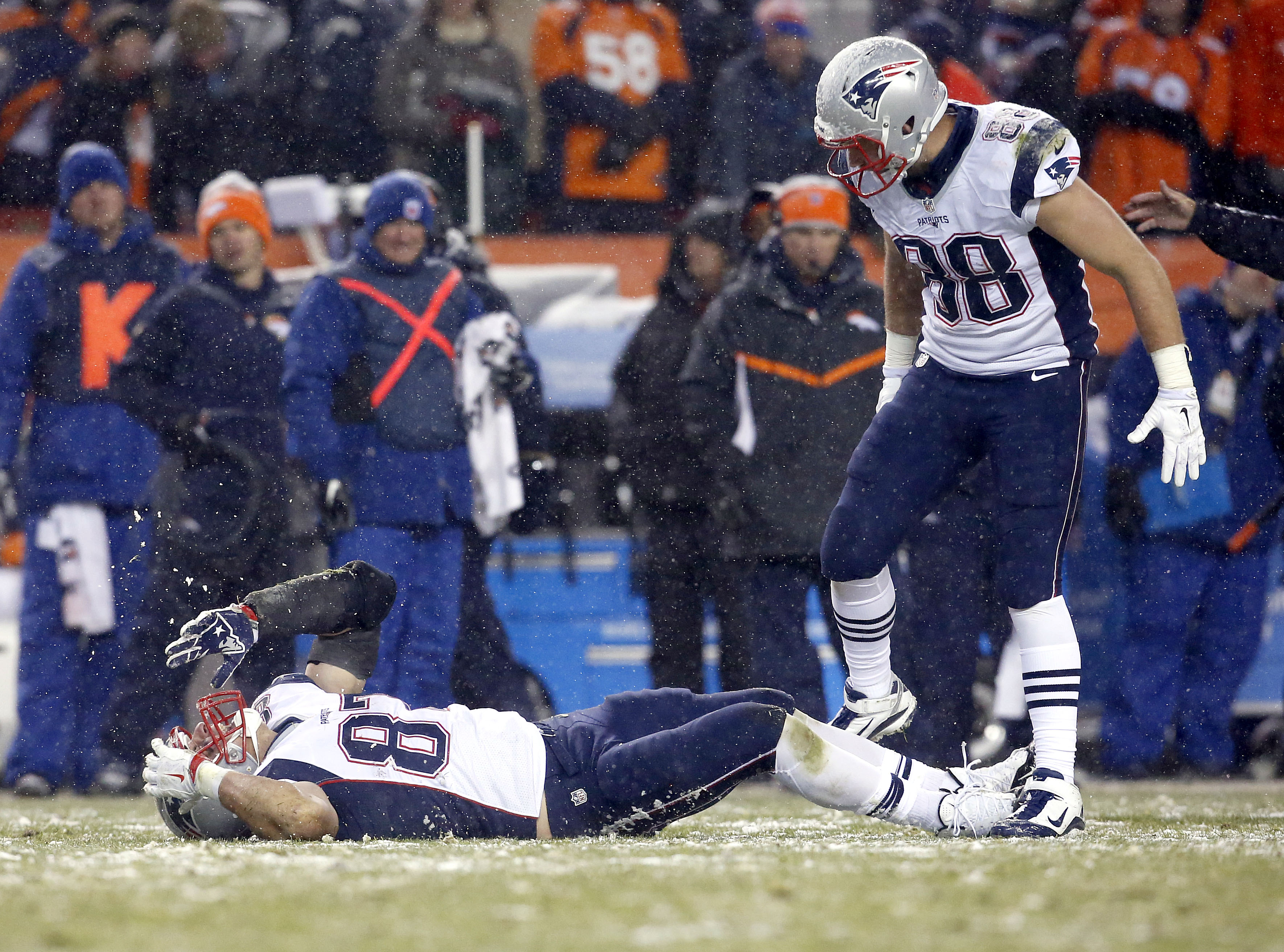 New England Patriots tight end Rob Gronkowski (87) lies injured on the field against the Denver Broncos as teammate tight end Scott Chandler (88) trees to help him up during the second half of an NFL football game, Sunday, Nov. 29, 2015, in Denver. (AP Ph
