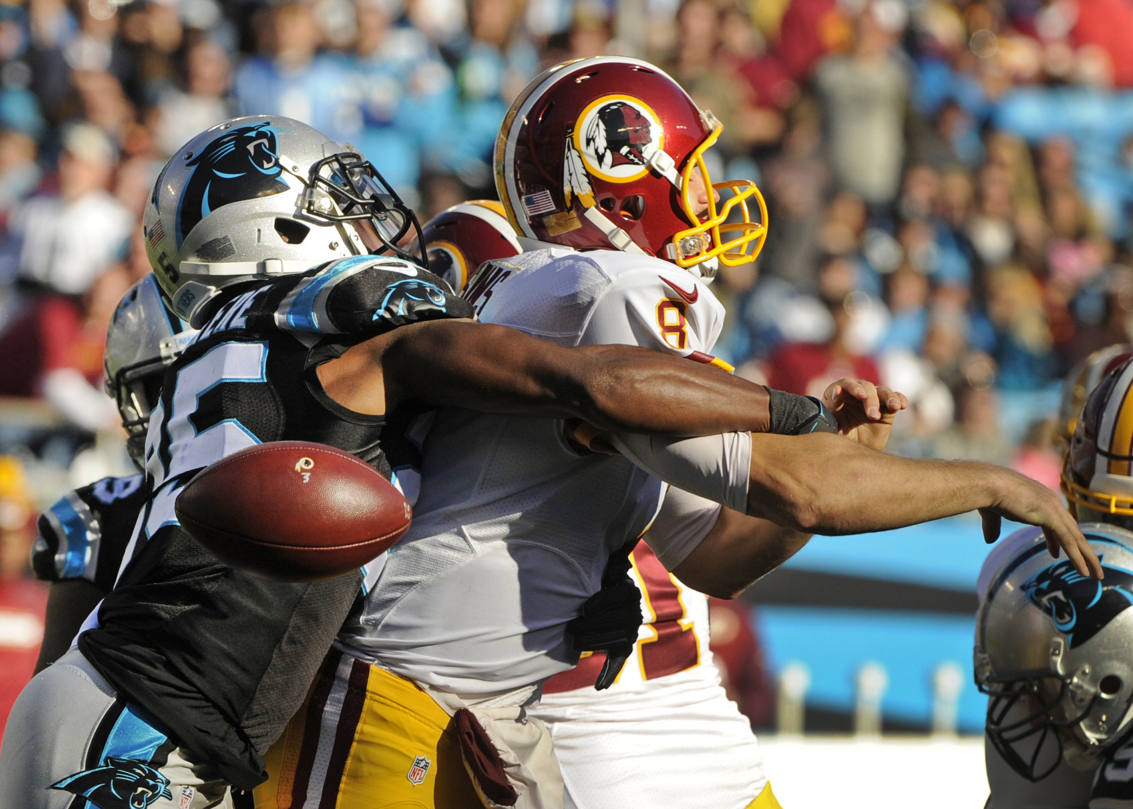 FILE - In this Nov. 22, 2015, file photo, Washington Redskins' Kirk Cousins, right, fumbles the ball as he is hit by Carolina Panthers' Bene' Benwikere, left, in the second half of an NFL football game in Charlotte, N.C. The Panthers recovered the ball. A