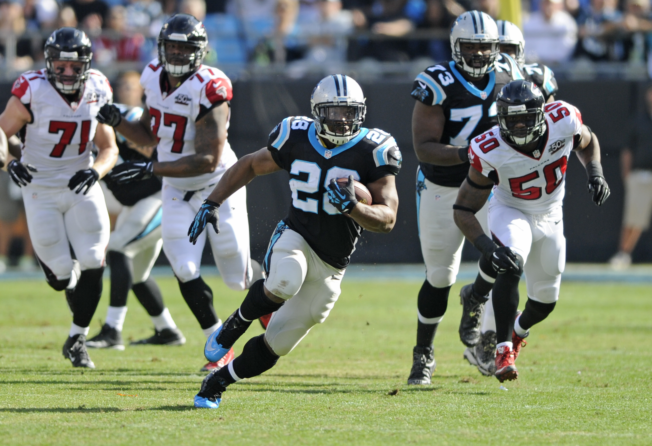 Carolina Panthers' Jonathan Stewart (28) runs past Atlanta Falcons players in the first half of an NFL football game in Charlotte, N.C., Sunday, Dec. 13, 2015. (AP Photo/Mike McCarn)