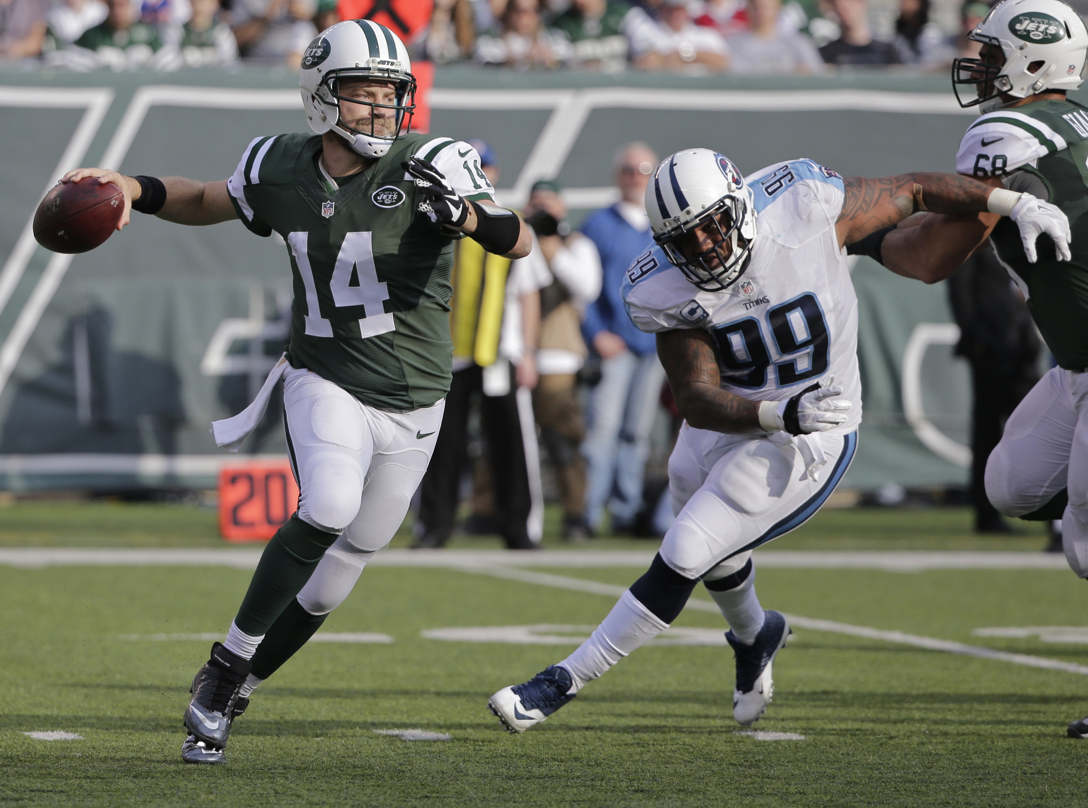 New York Jets quarterback Ryan Fitzpatrick (14) throws a pass away from Tennessee Titans' Jurrell Casey (99) during the first half of an NFL football game Sunday, Dec. 13, 2015, in East Rutherford, N.J.  (AP Photo/Julie Jacobson)