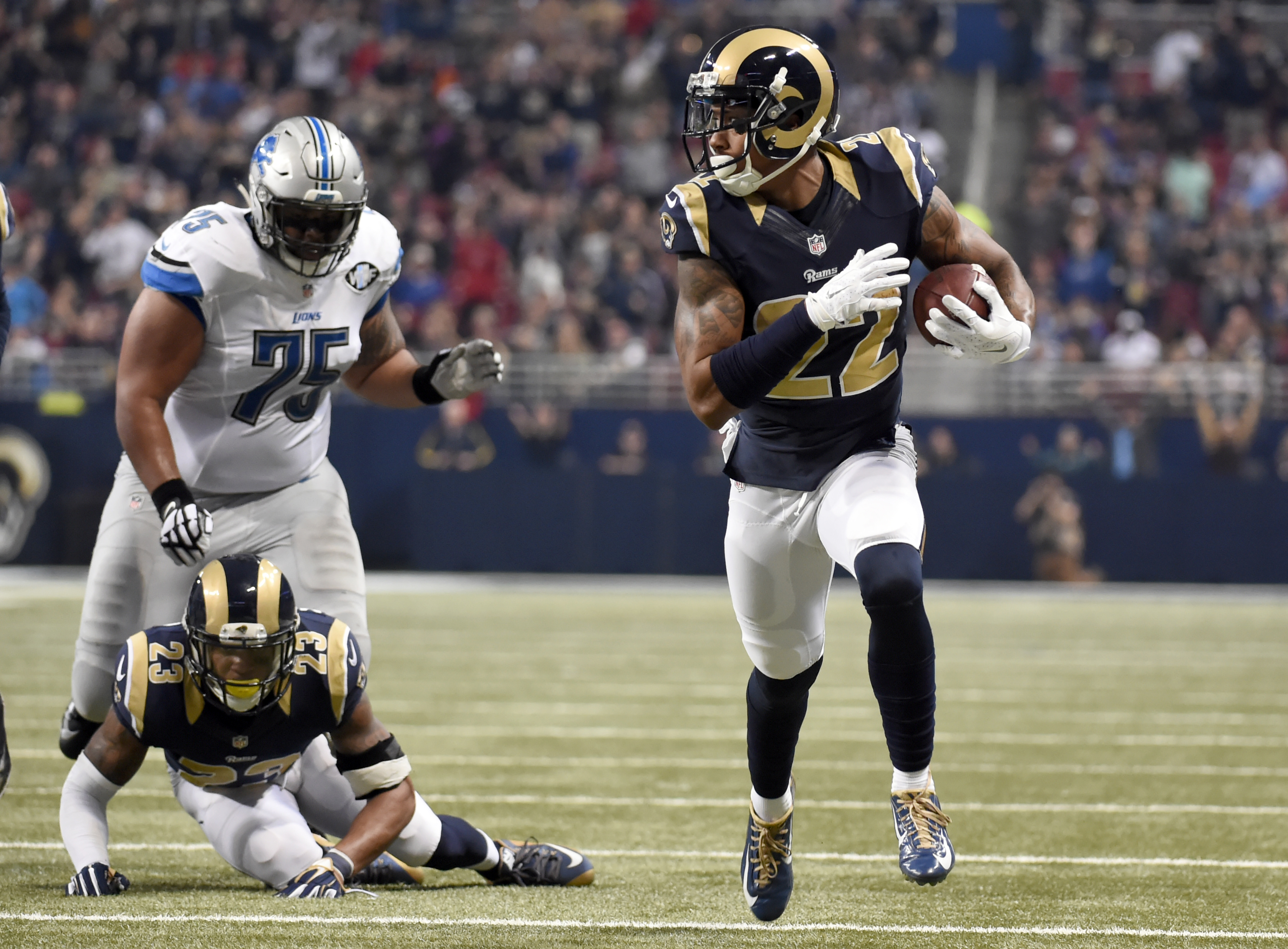 St. Louis Rams cornerback Trumaine Johnson, right, runs an interception back 58-yards for a touchdown as teammate Rodney McLeod (23) and Detroit Lions guard Larry Warford (75) watch during the second quarter of an NFL football game Sunday, Dec. 13, 2015,