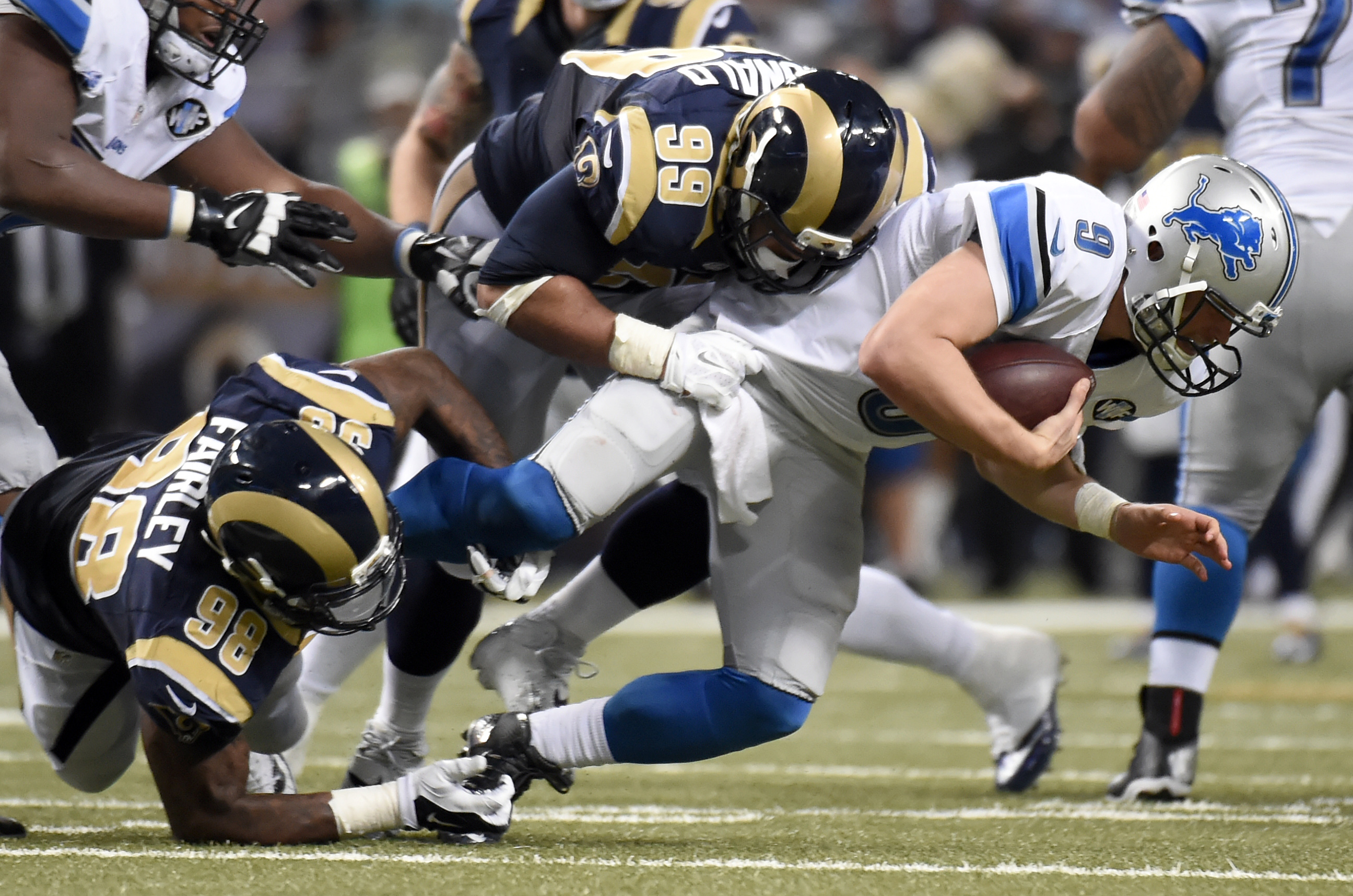 Detroit Lions quarterback Matthew Stafford, right, is sacked for a 7-yard loss by St. Louis Rams defensive tackle Aaron Donald (99) as Rams' defensive tackle Nick Fairley, left, gets in on the play during the fourth quarter of an NFL football game Sunday,