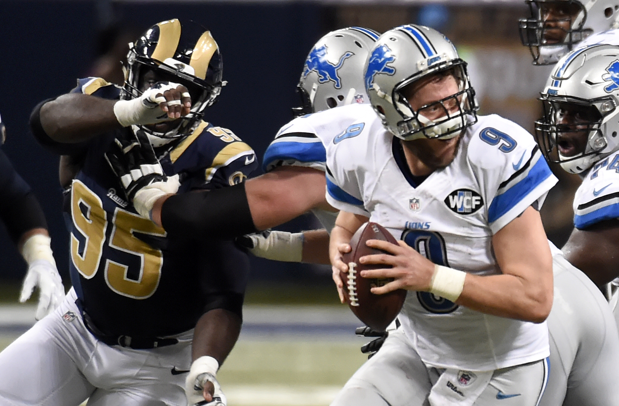 Detroit Lions quarterback Matthew Stafford, right, scrambles under pressure from St. Louis Rams defensive end William Hayes (95) during the fourth quarter of an NFL football game Sunday, Dec. 13, 2015, in St. Louis. (AP Photo/L.G. Patterson)