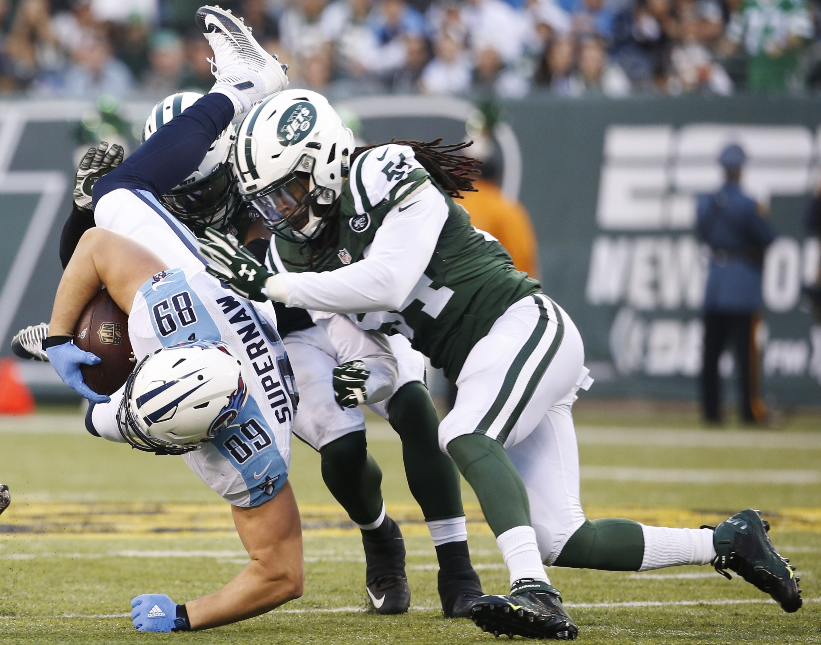 New York Jets inside linebacker Demario Davis (56) tackles Tennessee Titans' Phillip Supernaw (89) during the second half of an NFL football game Sunday, Dec. 13, 2015, in East Rutherford, N.J. The Jets won 30-8.  (AP Photo/Julio Cortez)