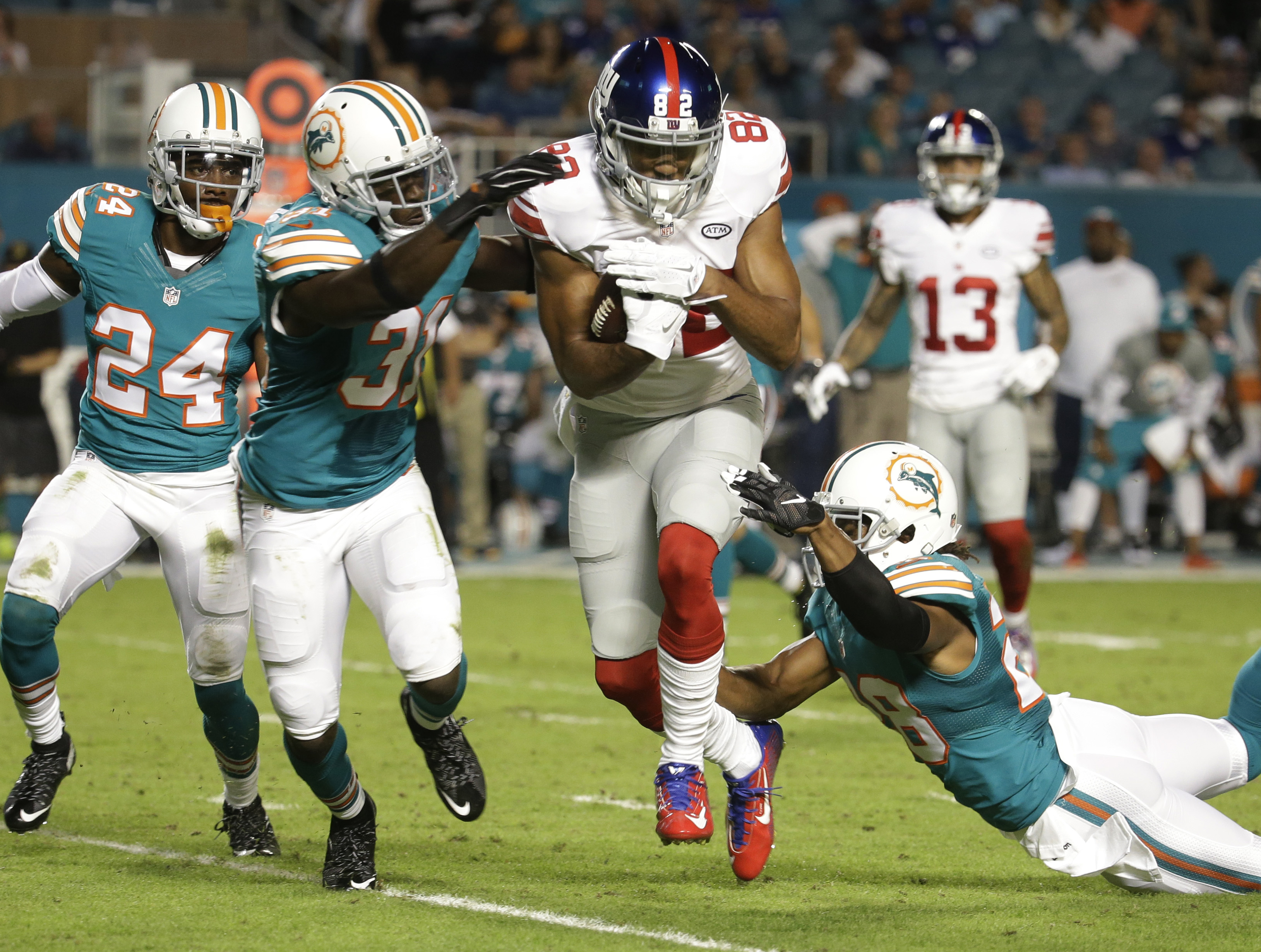 Miami Dolphins free safety Michael Thomas (31) and cornerback Bobby McCain (28) attempt to stop New York Giants wide receiver Rueben Randle (82), during the first half of an NFL football game, Monday, Dec. 14, 2015, in Miami Gardens, Fla. to the left is M