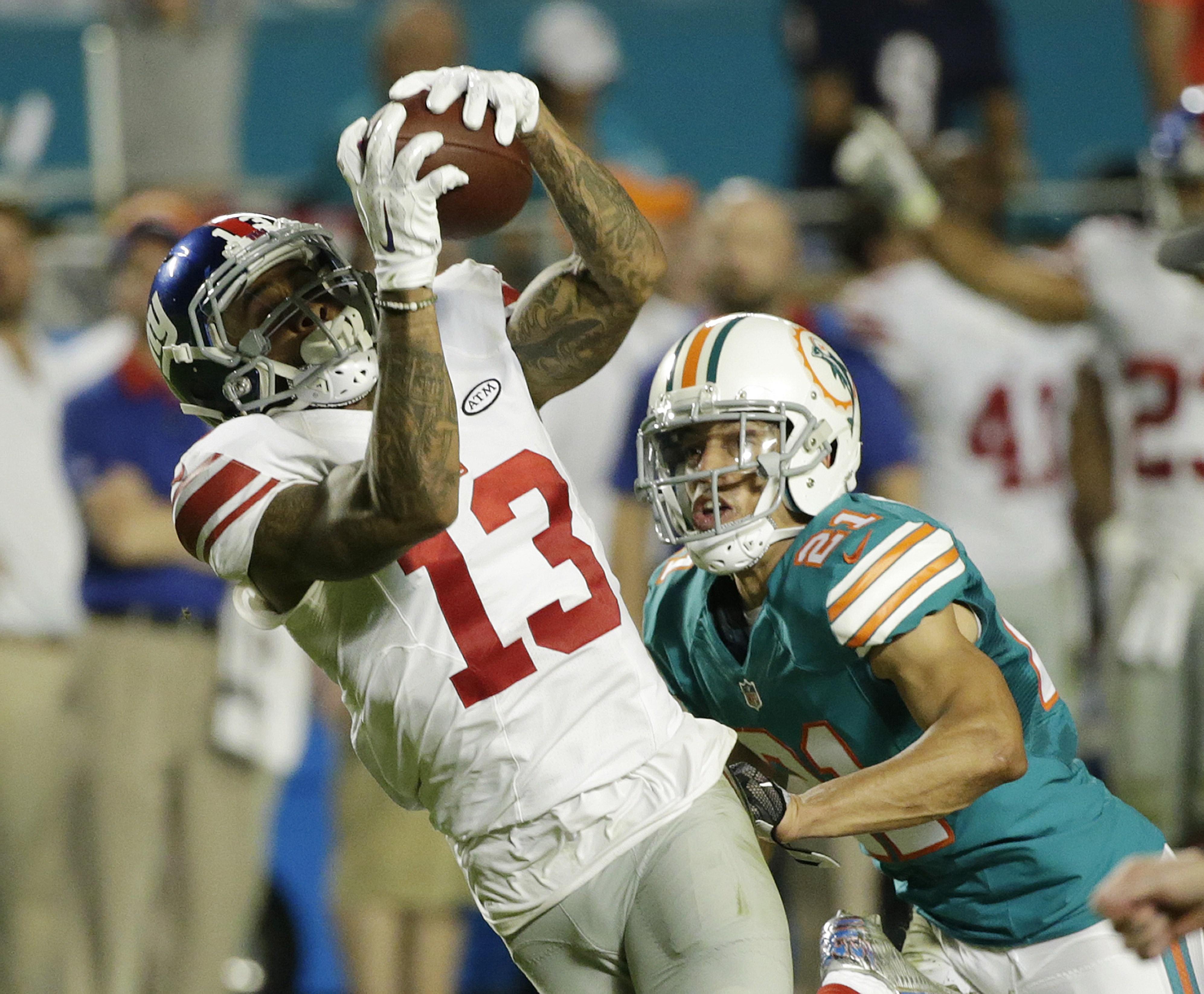 New York Giants wide receiver Odell Beckham (13) makes a catch as Miami Dolphins cornerback Brent Grimes (21) defends, during the first half of an NFL football game, Monday, Dec. 14, 2015, in Miami Gardens, Fla.  (AP Photo/Wilfredo Lee)