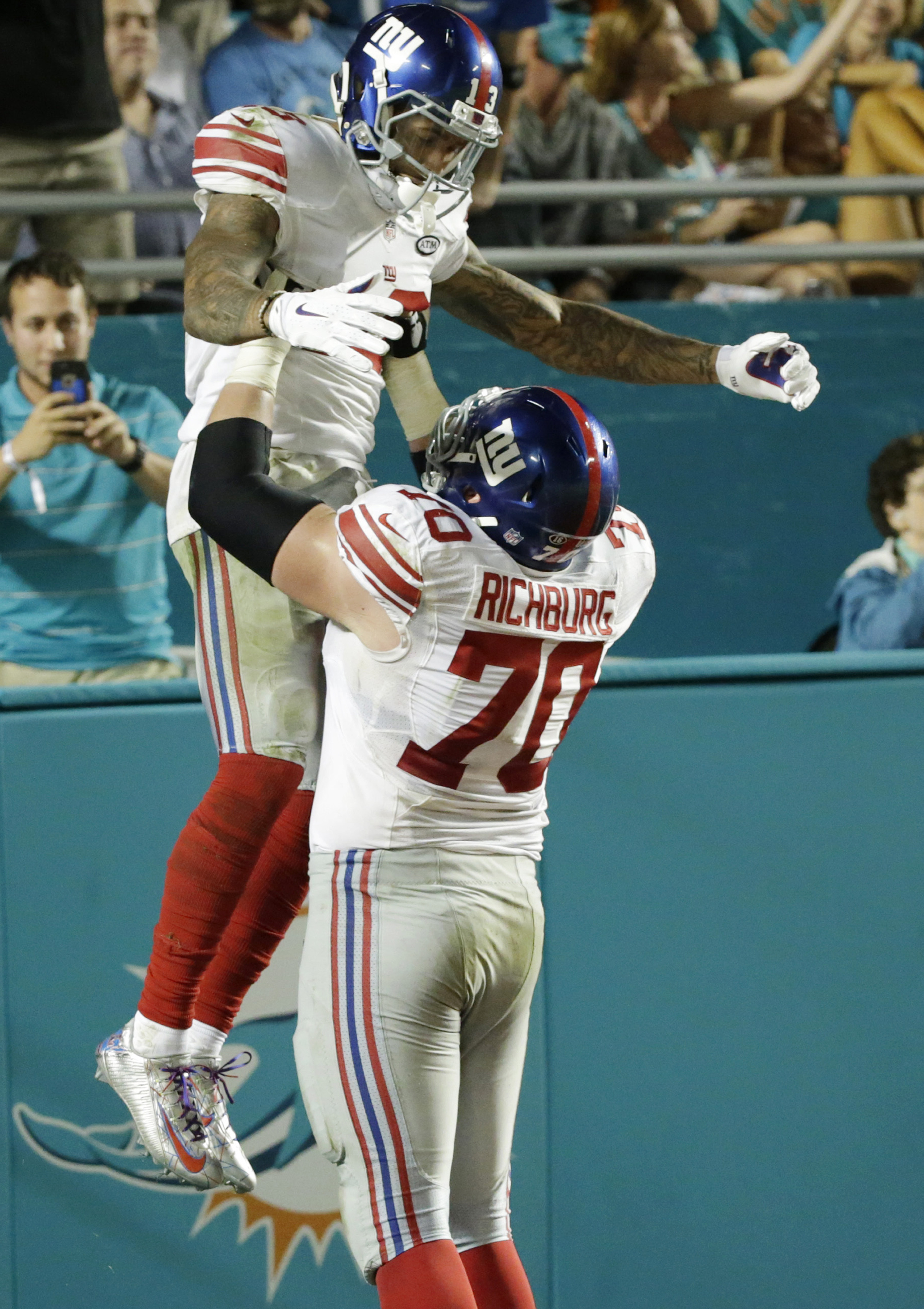 New York Giants wide receiver Odell Beckham (13) is lifted by center Weston Richburg (70) after Beckham scored a touchdown during the second half of an NFL football game against the Miami Dolphins, Monday, Dec. 14, 2015, in Miami Gardens, Fla.  (AP Photo/