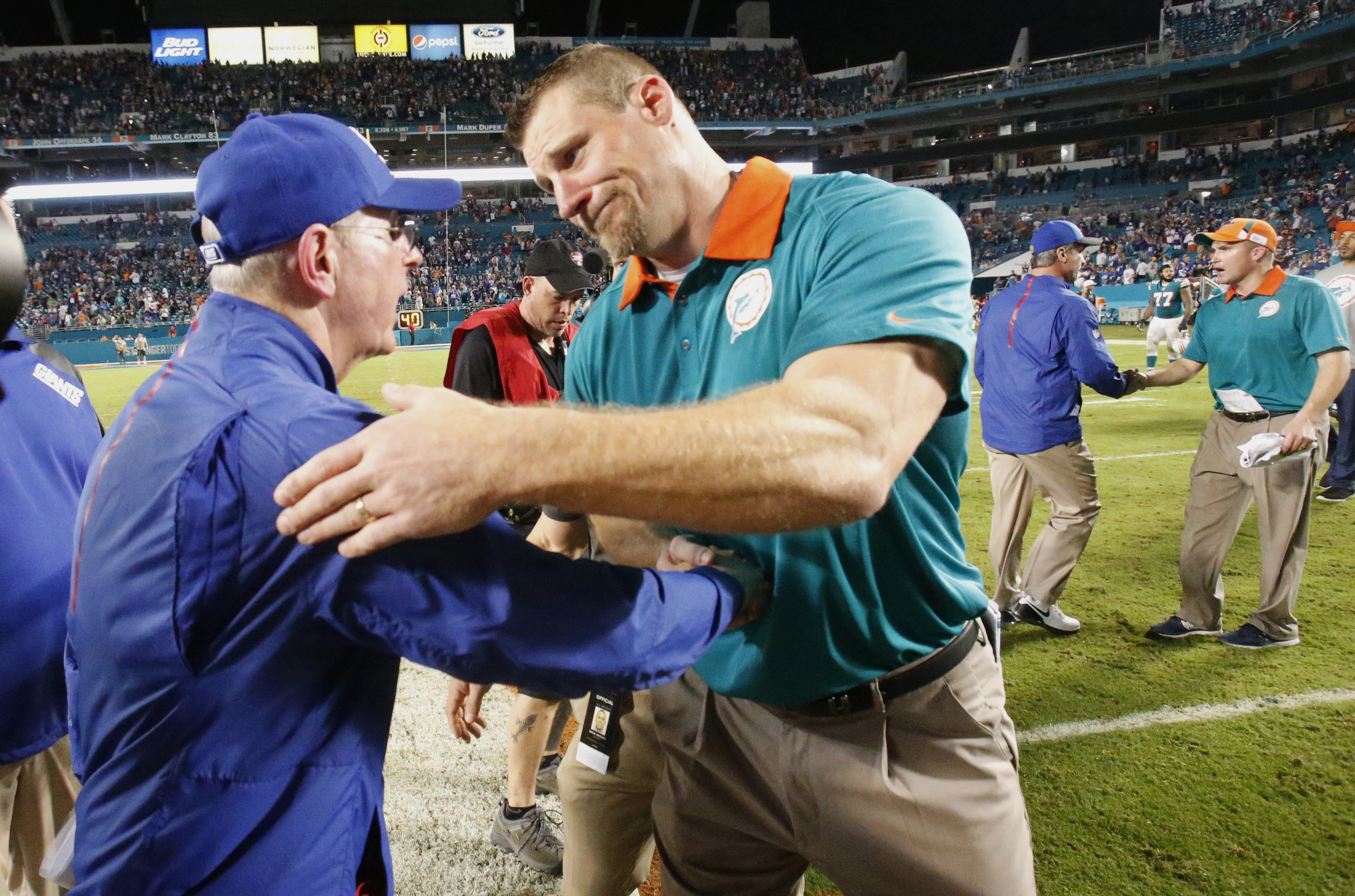New York Giants head coach Tom Coughlin, left, and Miami Dolphins interim head coach Dan Campbell greet at the end of an NFL football game, Monday, Dec. 14, 2015, in Miami Gardens, Fla. The Giants defeated the Dolphins 31-24. (AP Photo/Wilfredo Lee)